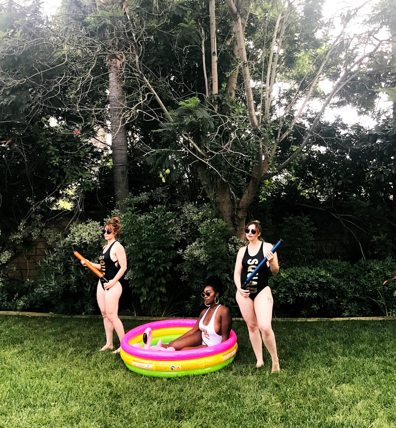 """Three women posing in """"bride"""" and """"squad"""" bathing suits"""