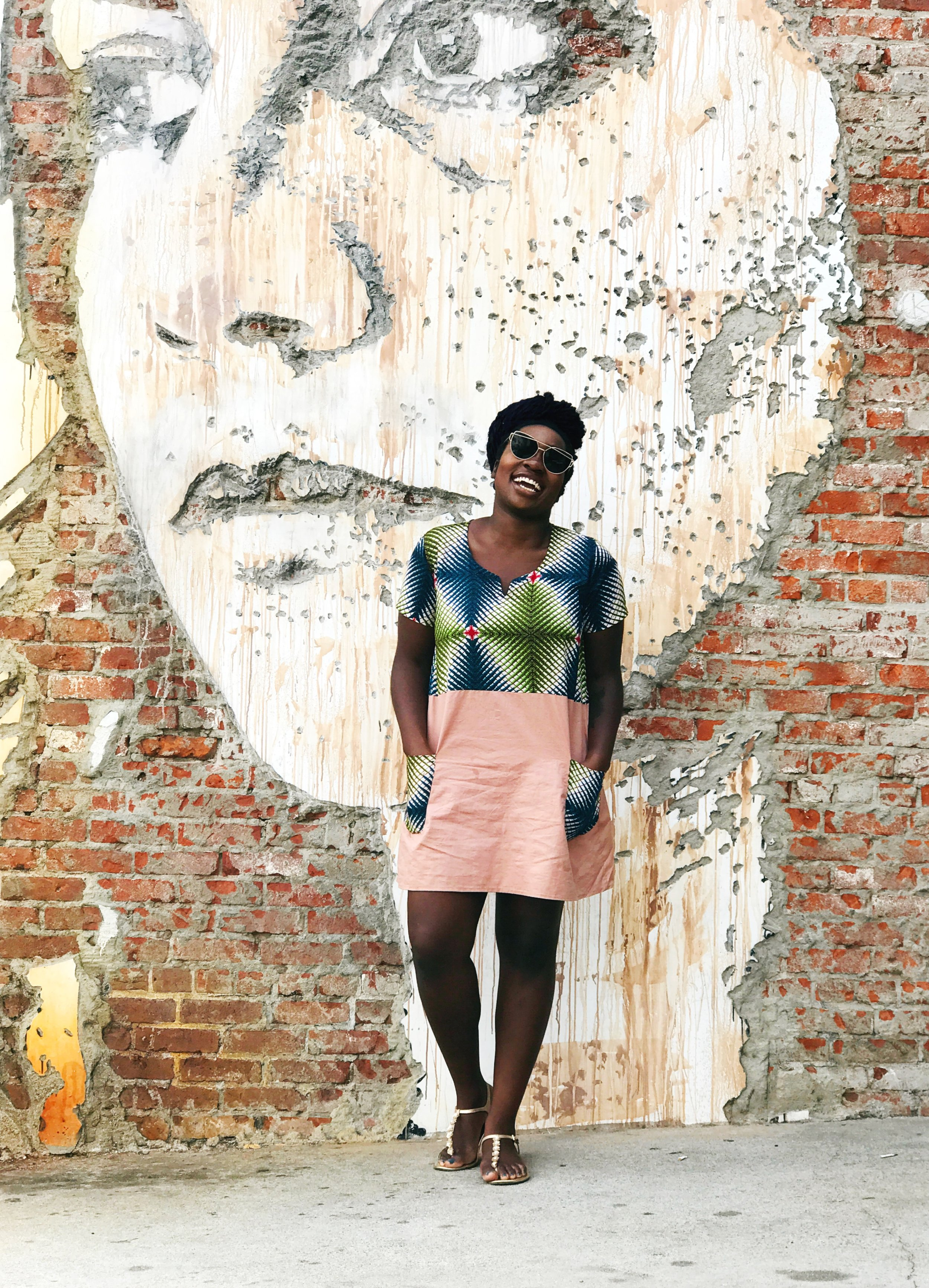 Femi laughing in African dress in front of wall #BlackGirlMagic