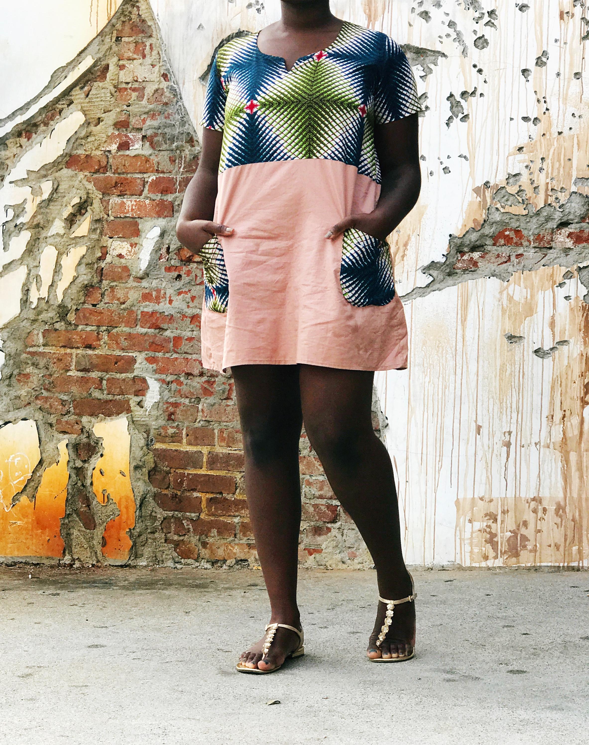 Black woman wearing pink and ankara dress and gold sandals.