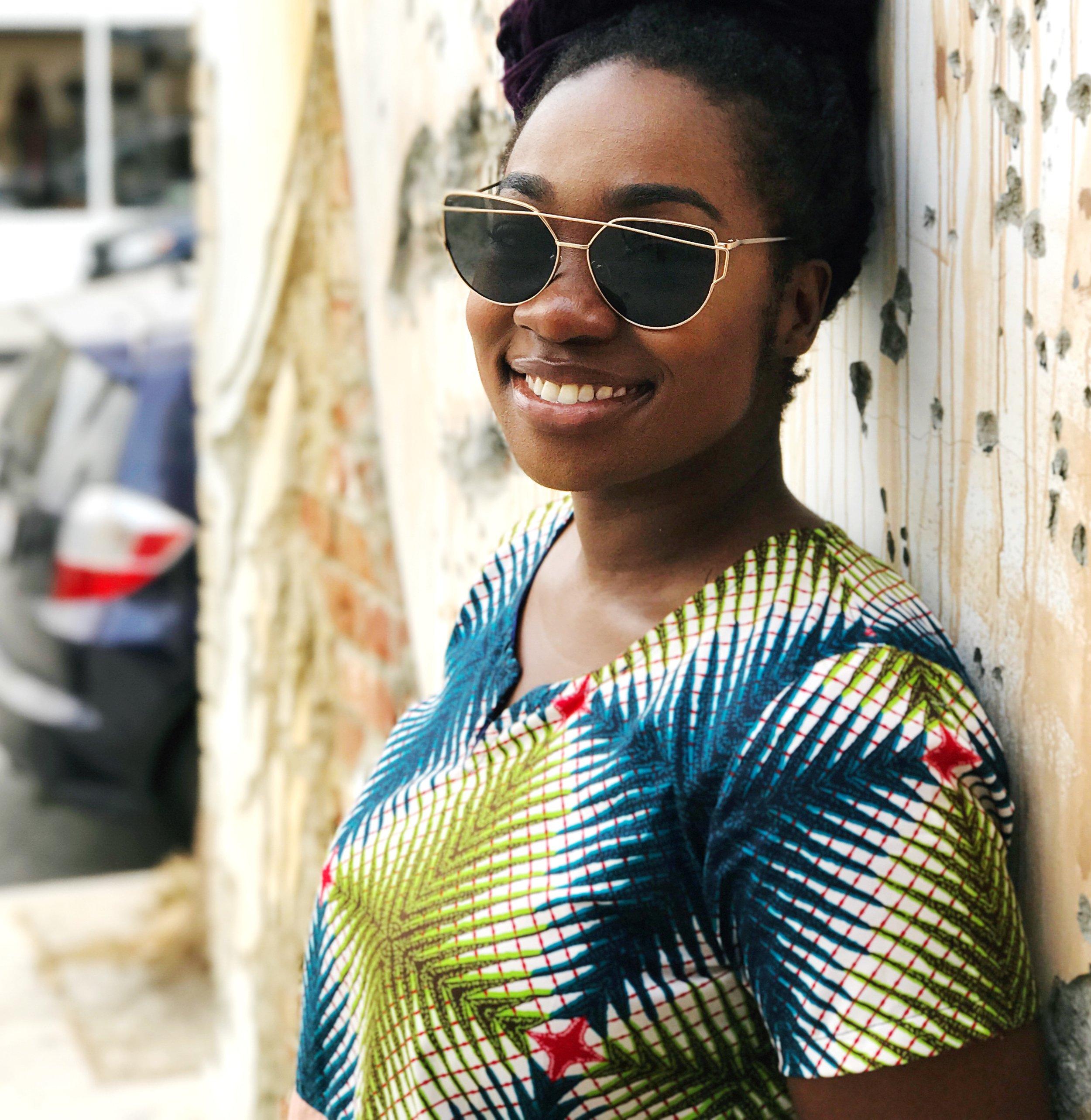 Femi smiling at camera wearing sunglasses and ankara print dress