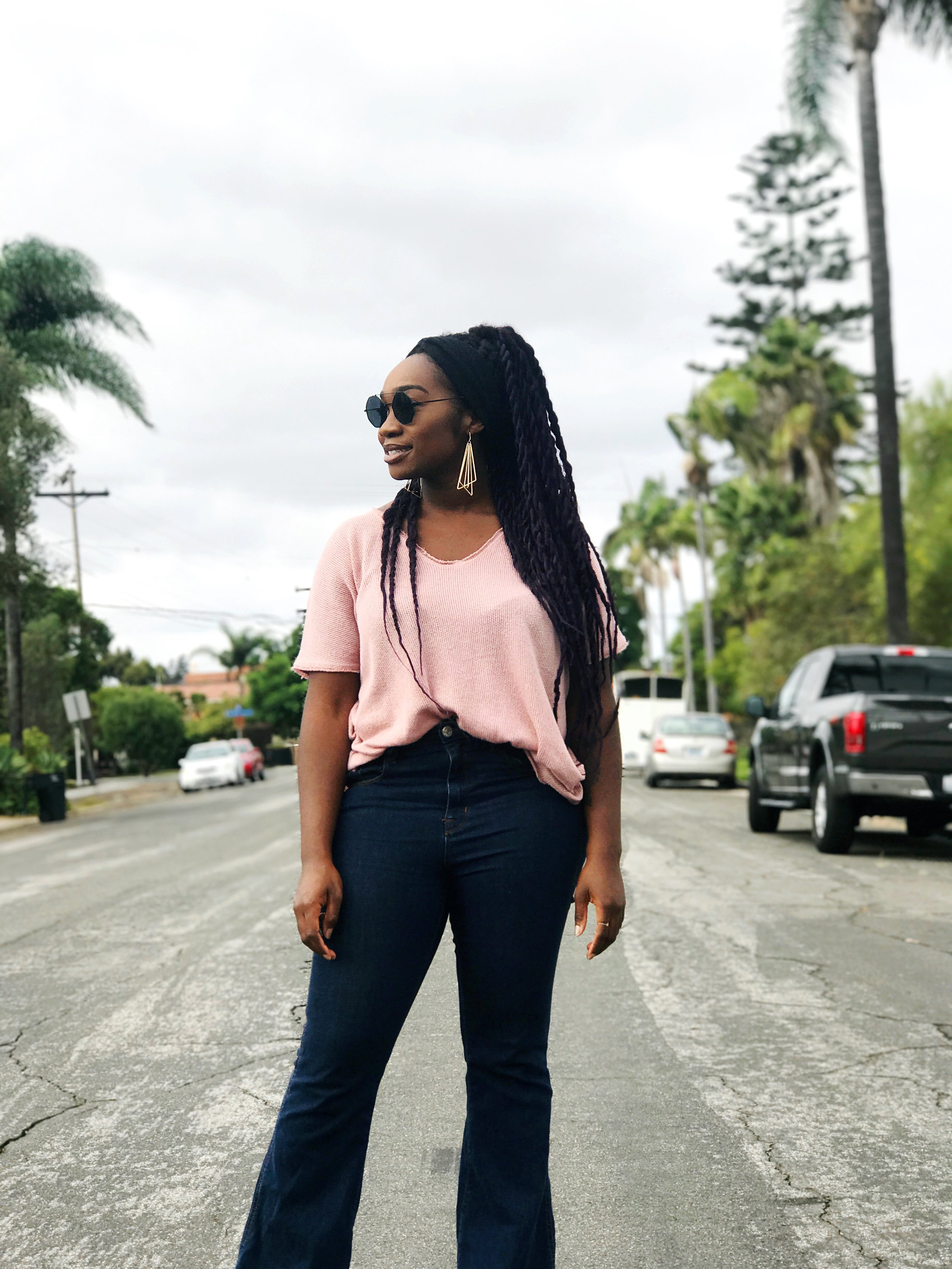 Black woman wearing pink shirt half tucked into bell bottom jeans #blackgirlmagic