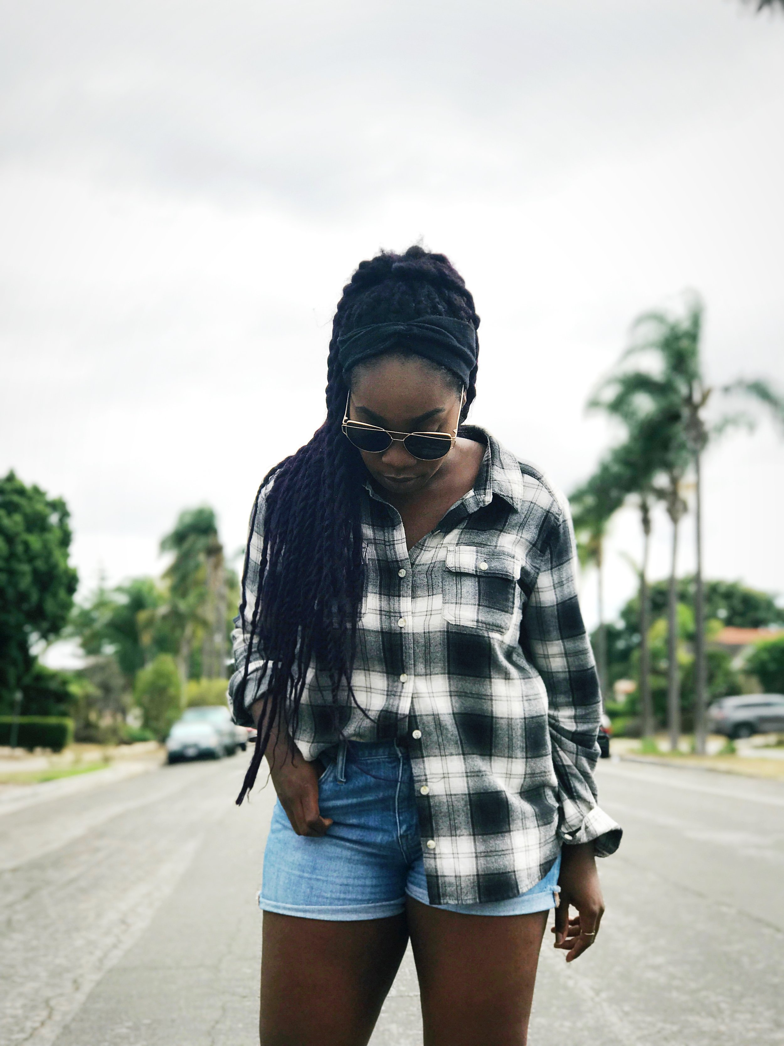 Femi wearing flannel and jean shorts in middle of street.