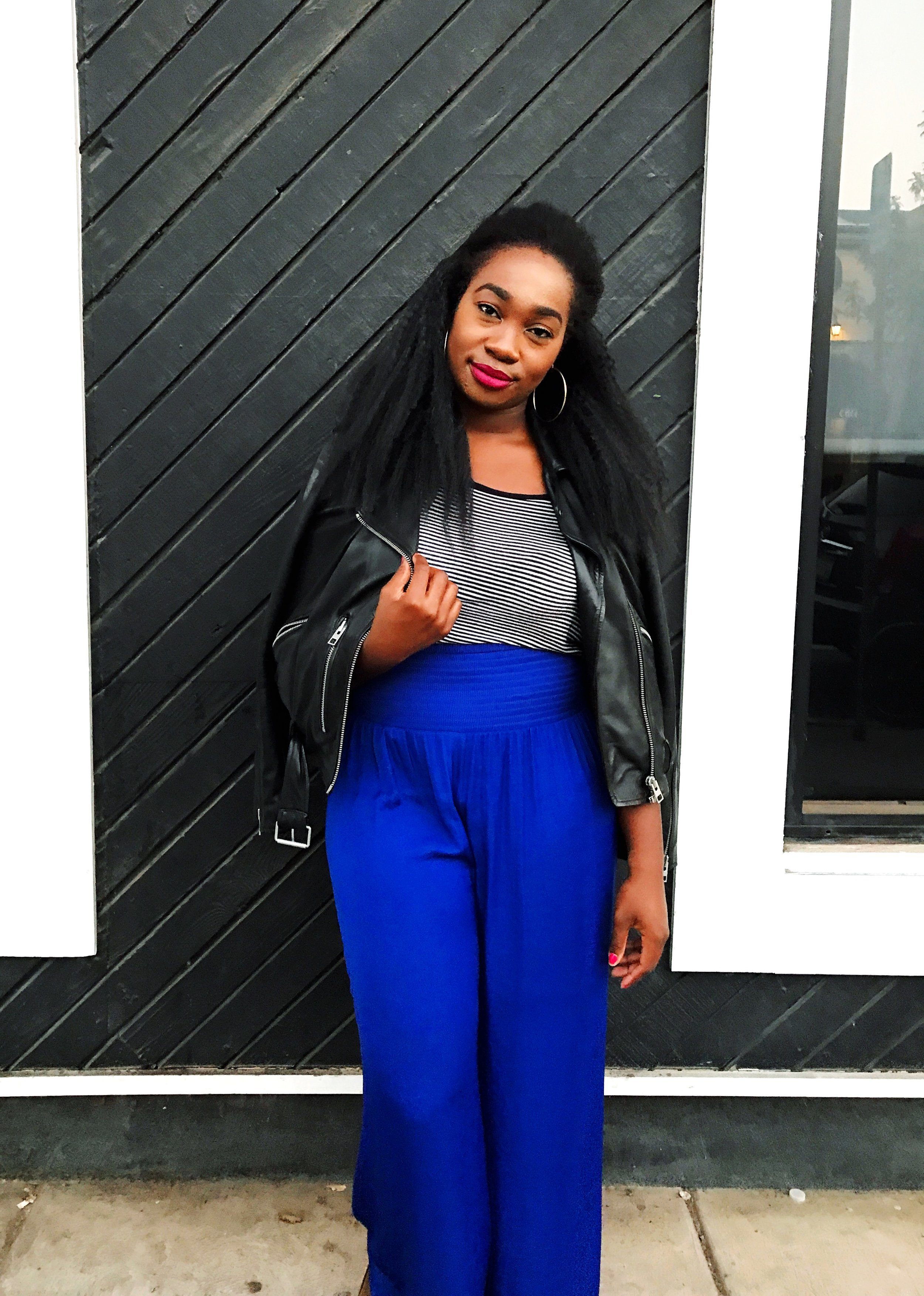 Femi wearing All Saints leather jacket and blue wide-leg pants