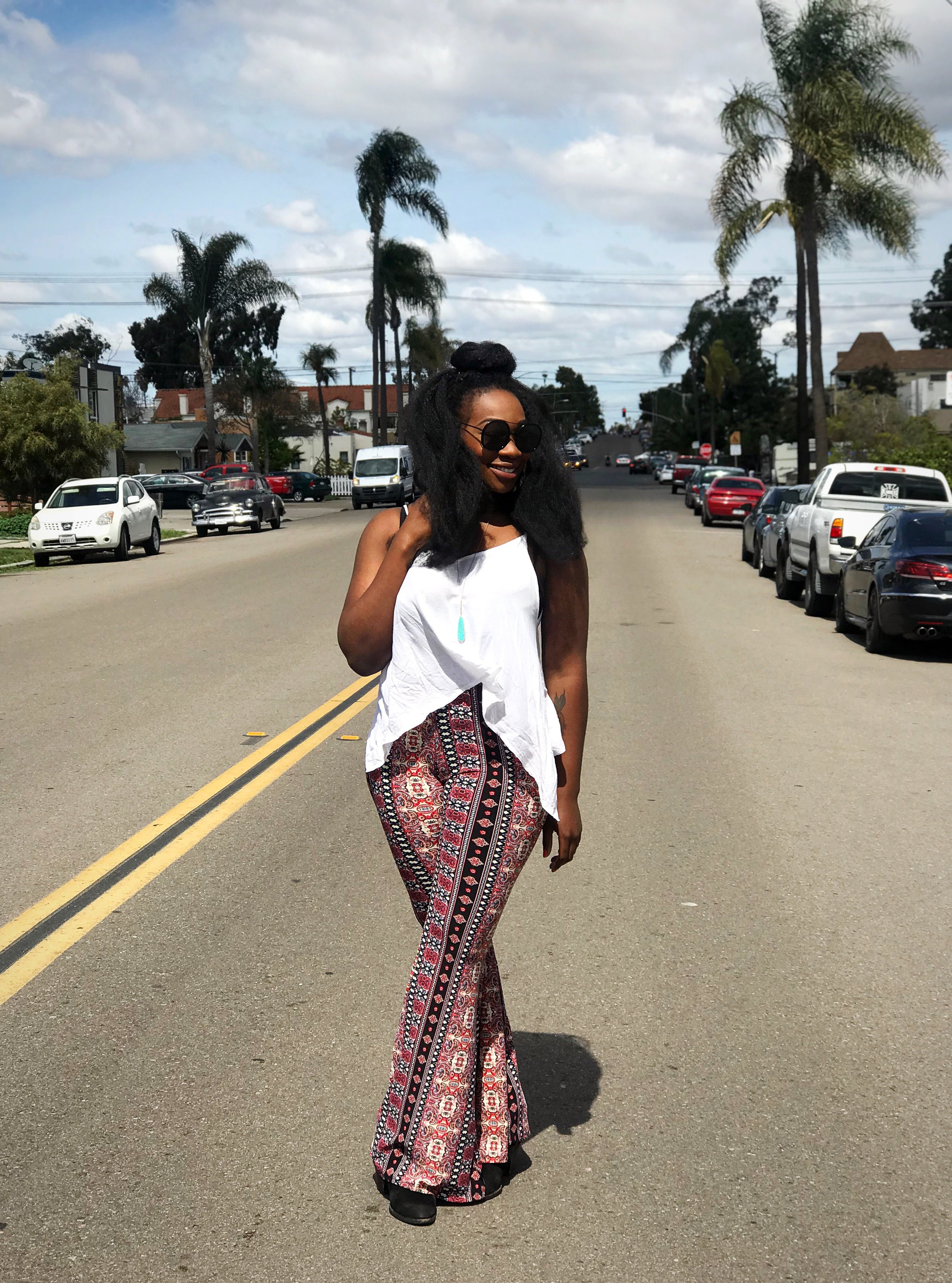 Image: Femi standing in the street wearing printed bell bottom pants, white top, turquoise stone necklace