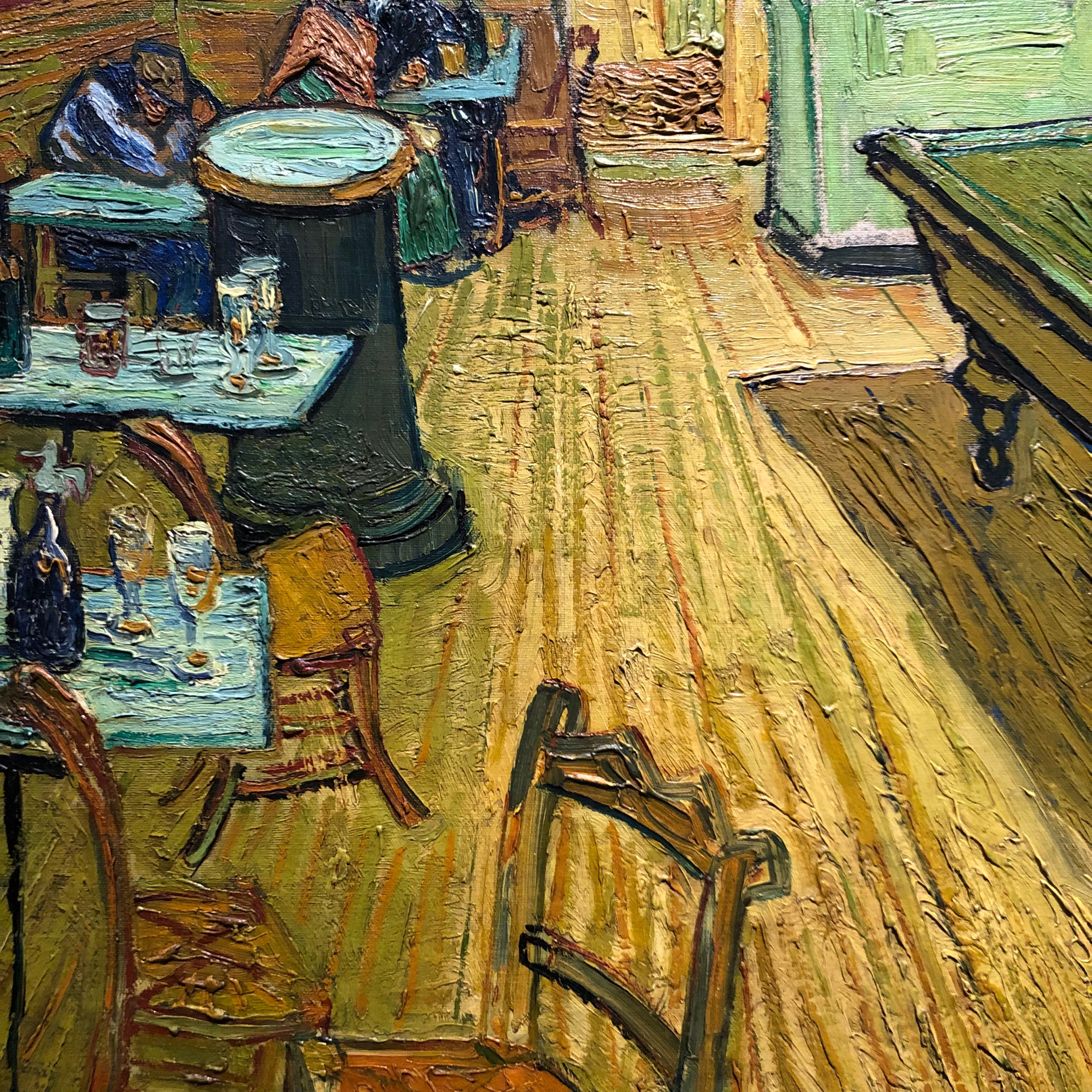 A detail from  The Night Café , showing abandoned tables and a drinker with his face in his arms.