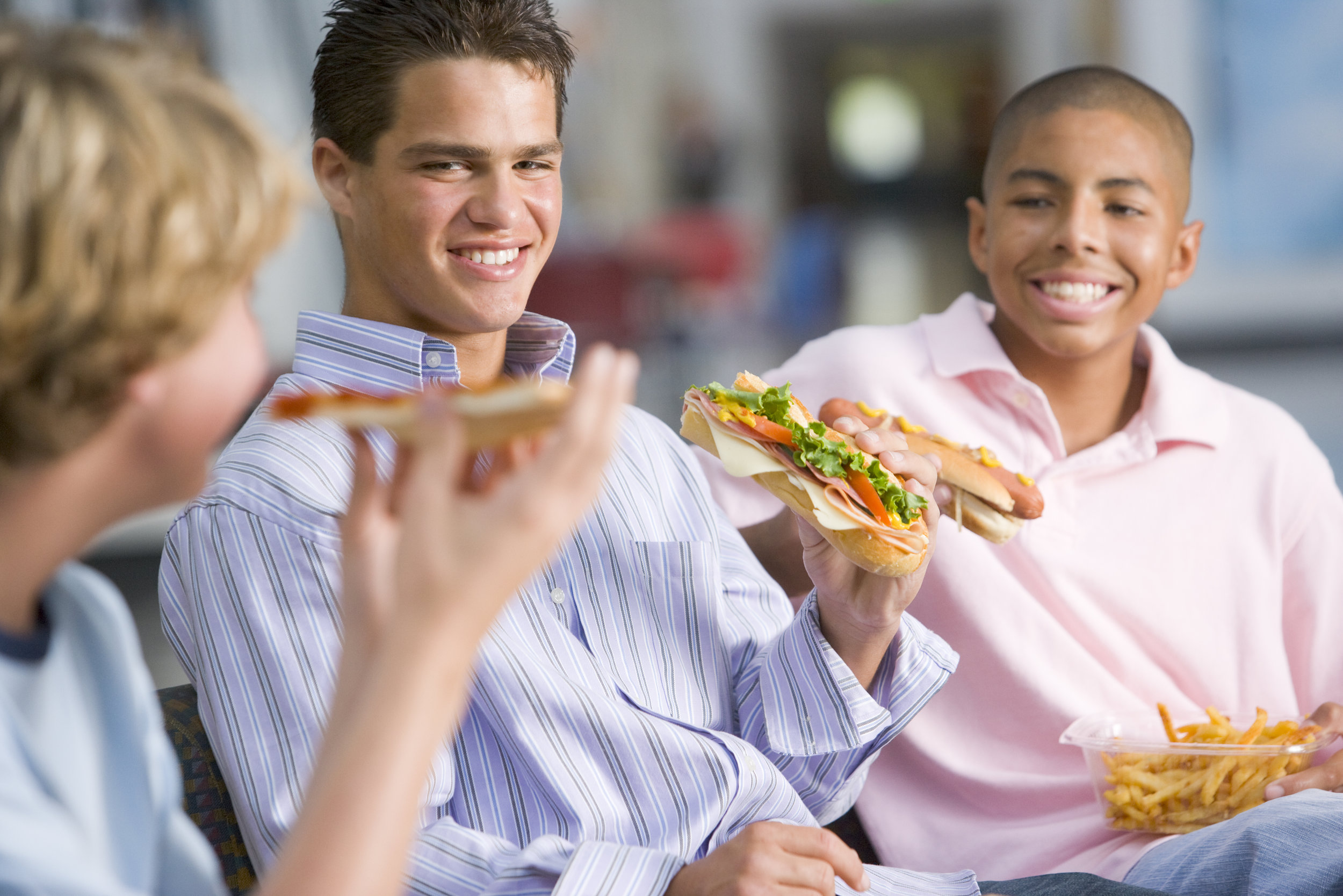 teenage-boys-enjoying-fast-food-lunches-together_BYQe0Crs.jpg
