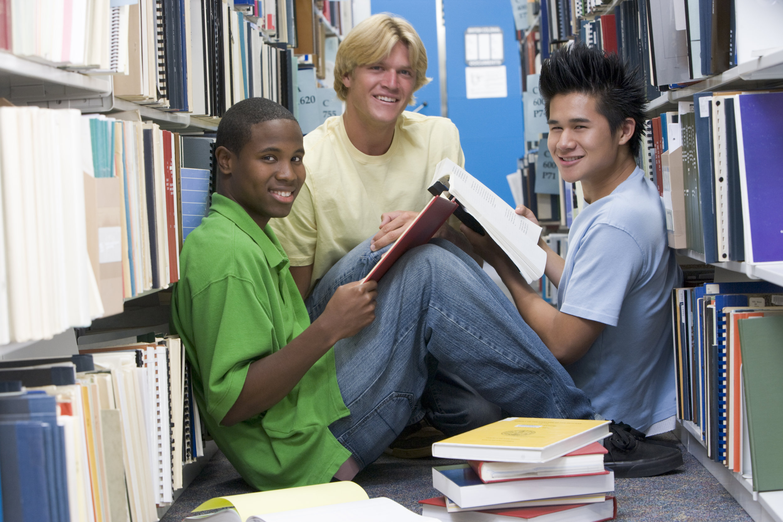 group-of-three-male-students-sitting-on-floor-of-library-surrounded-by-books_HFtNGBRSs.jpg