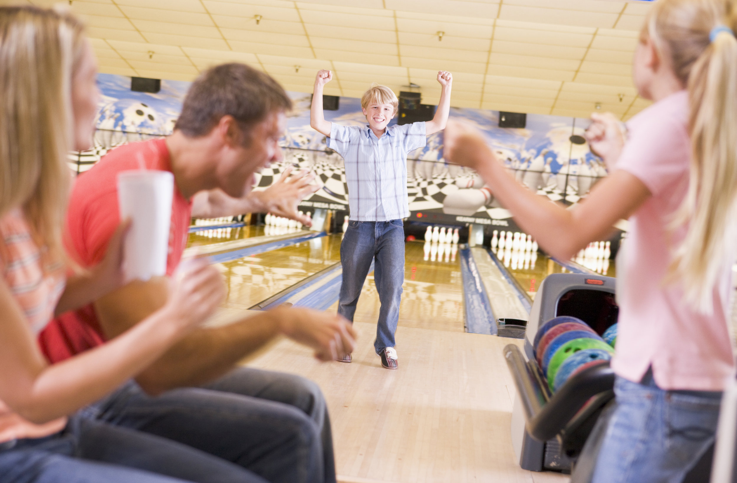 family-in-bowling-alley-cheering-and-smiling_HY0FN6ABj.jpg