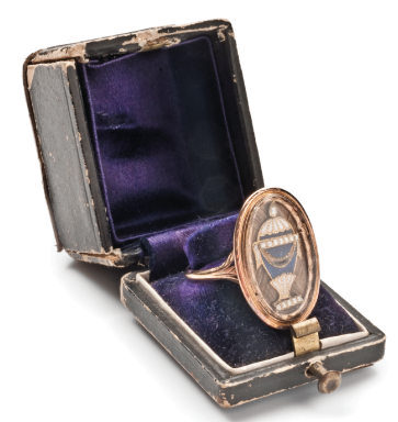 Mourning ring in original box dated 22nd April 1784. The gold, pearl and blue/white enamel urn sits upon hairwork