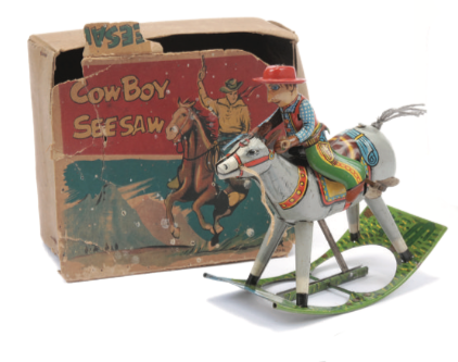 A rare 1950s novelty 'Cowboy See-Saw' made by C K Toys. A clockwork motor makes the horse rock back and forth, and the cowboy has a hinged arm so it appears that he's firing his gun. Sold for £96 in August 2014