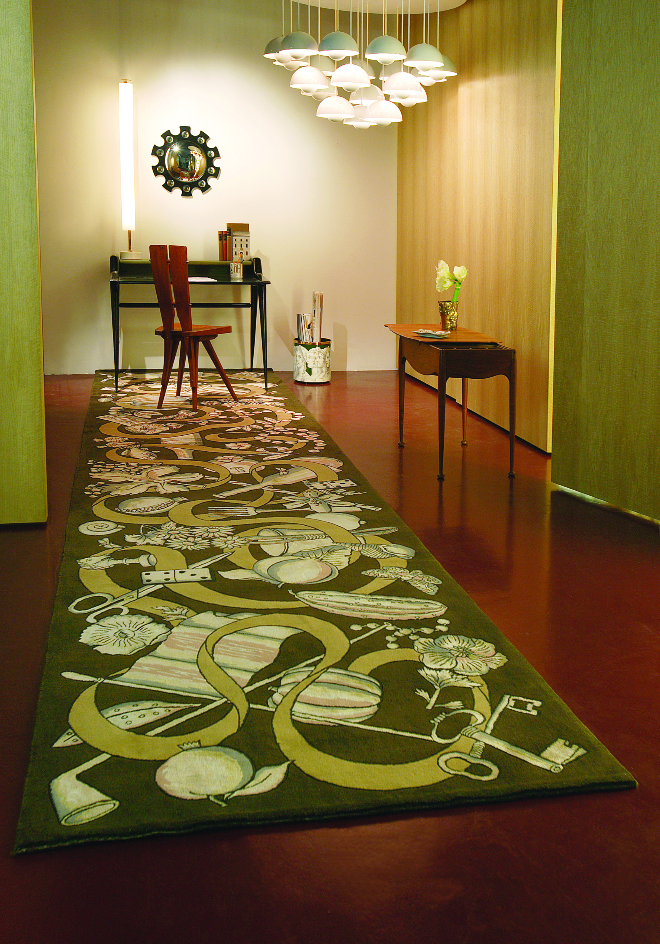 Rug 'Nastro' (ribbon) by Roubini Rugs in wool and silk, hand knotted. To the right of the rug is a paper basket 'Profili di donna' on green. On the desk is 'Stumenti da disegni' a porcelain pencil holder and a bookend 'Architettura'. The mirror is 'Van Eyck'. With the exception of the desk all are by Fornasetti