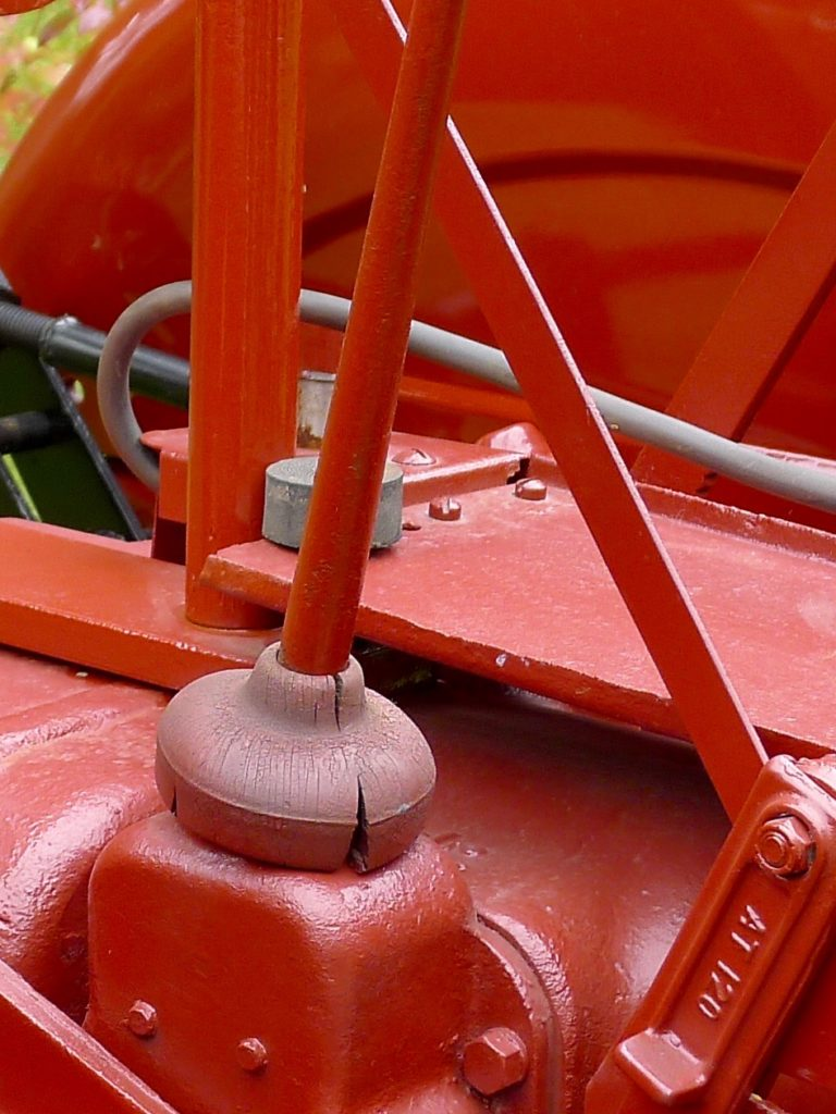 The rubber waterproofing around the base of this gear shift lever was intended to prevent water from getting into the transmission and gear train, but it is cracked and deteriorating. Some tractors have a factory rubber seal under the shift pattern, which can also fail.