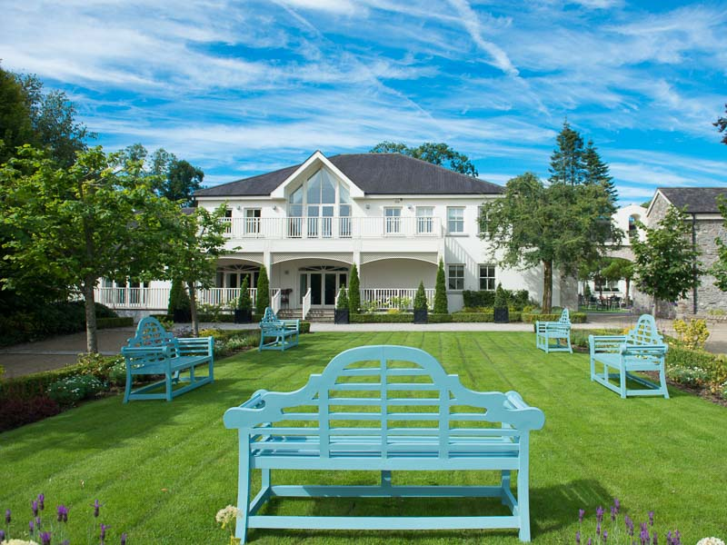 Tulfarris Hotel and Golf Resort exterior of manor house with benches.jpg