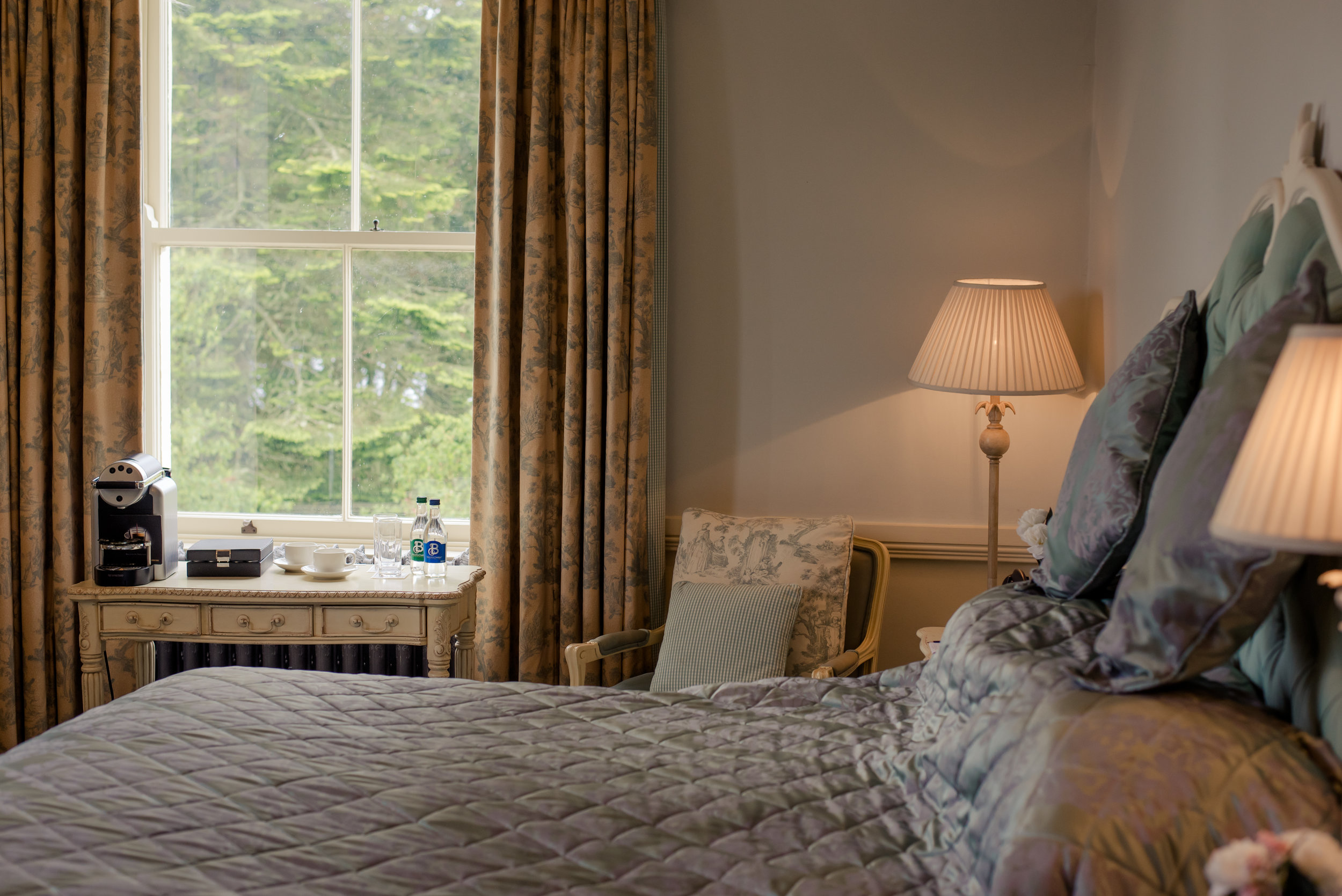 Tulfarris Hotel & Golf Resort Manor House bedroom with bedise lamps and beautiful window view.jpg