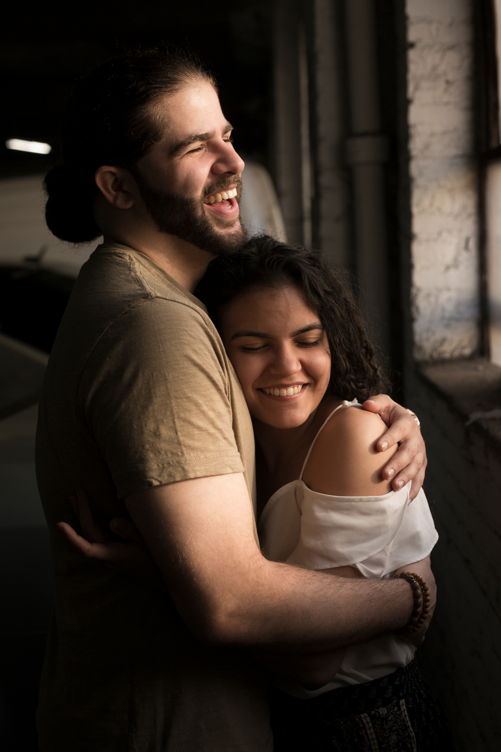 couple laughing and hugging in a parking garage