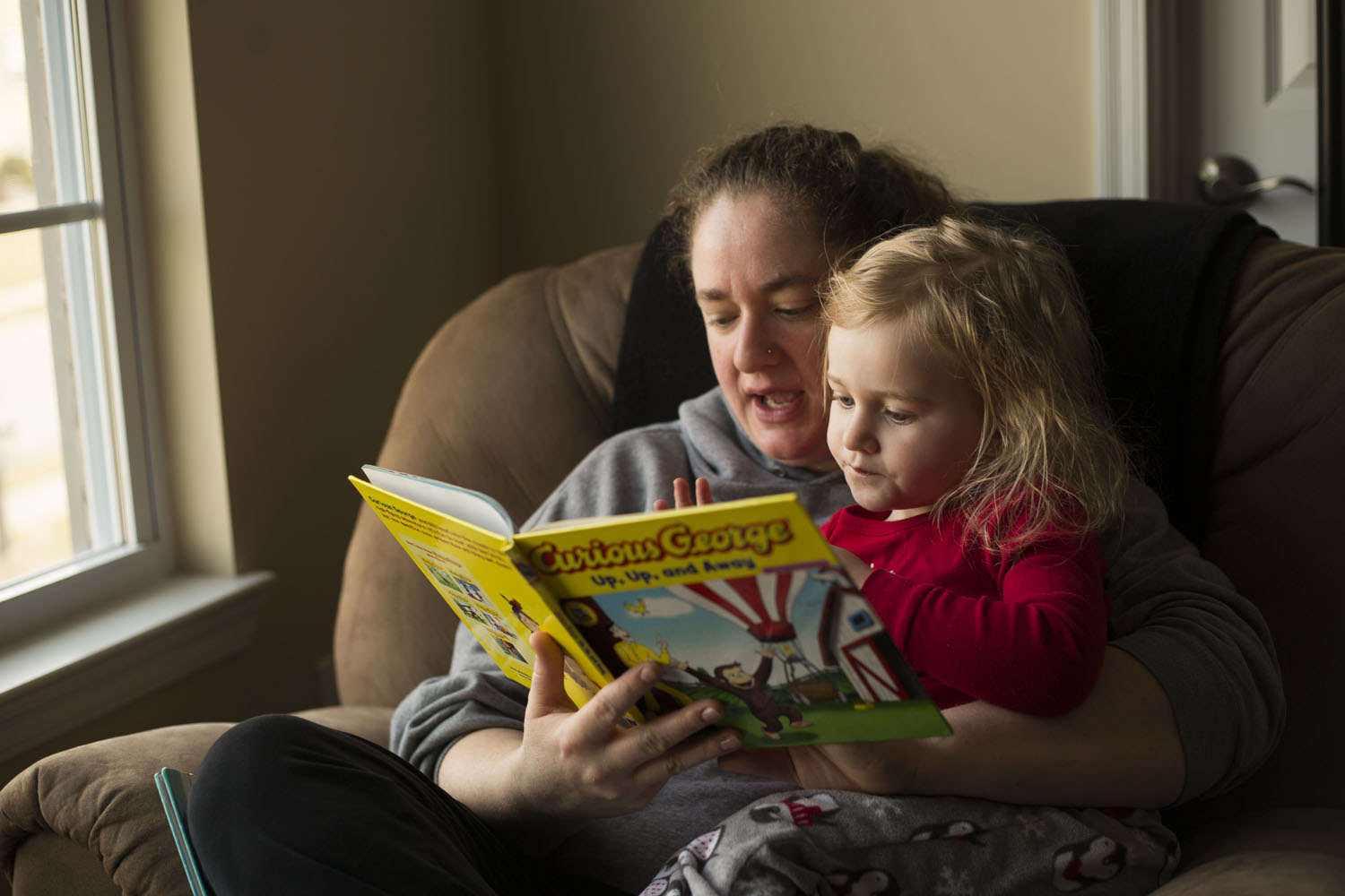 mom reading curious george to her daughter brooklyn heights family photographer