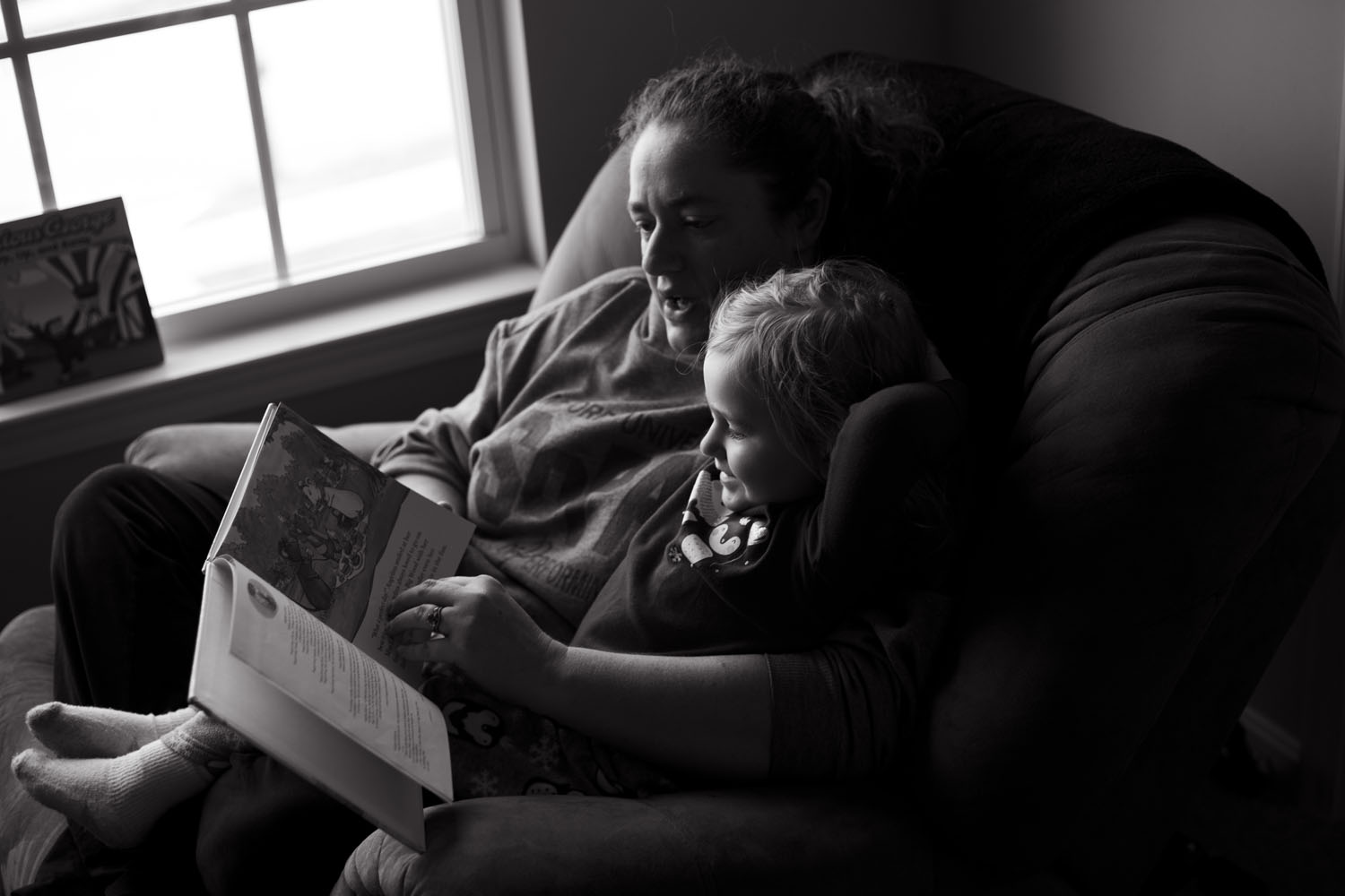 mom and daughter reading a book on the sofa