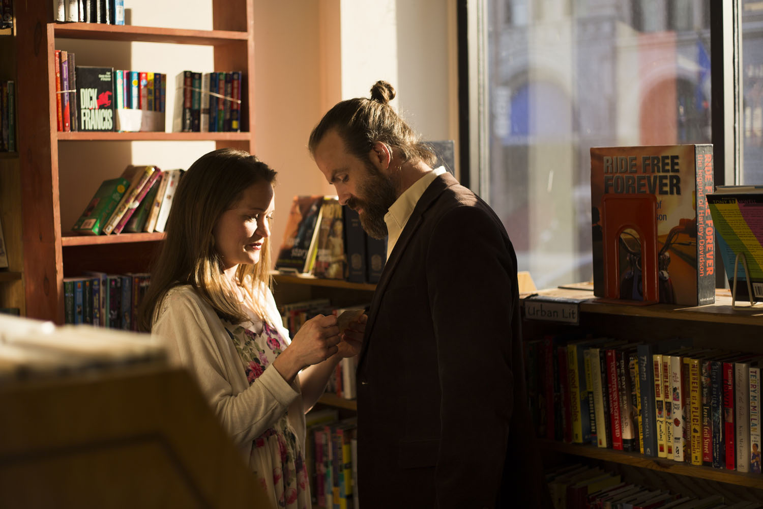 couple reading a note in a bookstore sunlight golden hour