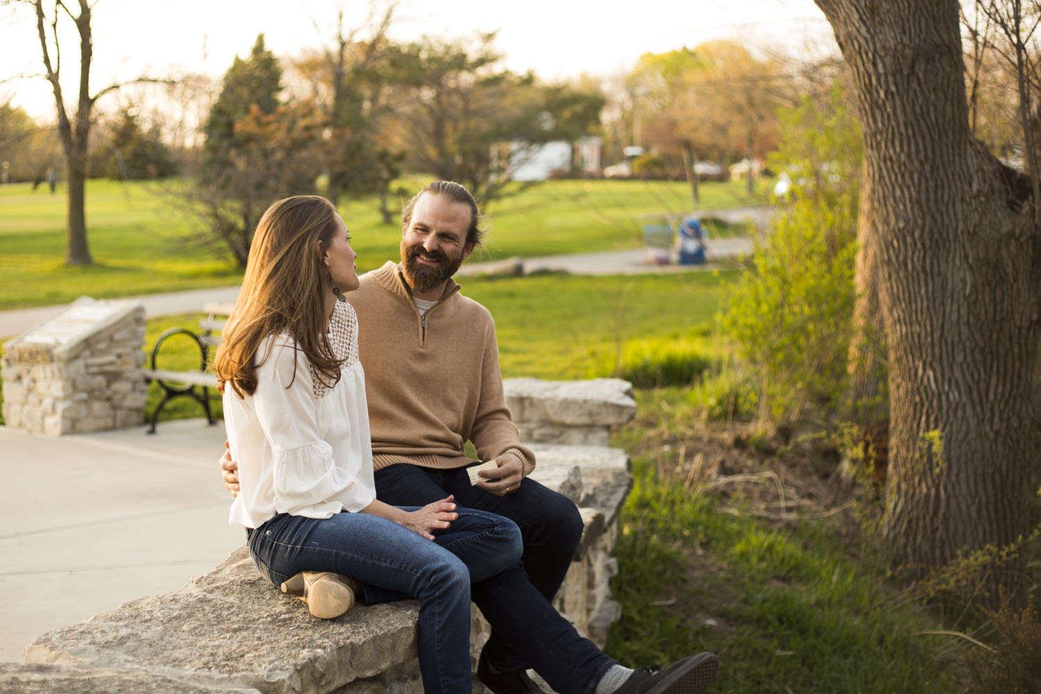 couple sitting on a stone bench park engagement shoot