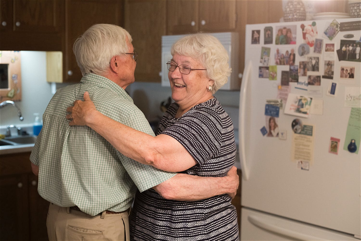 couple with gray hair dancing in the kitchen