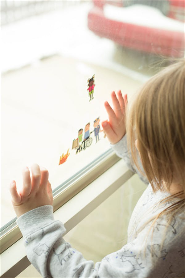 girl looking at a window family photographer