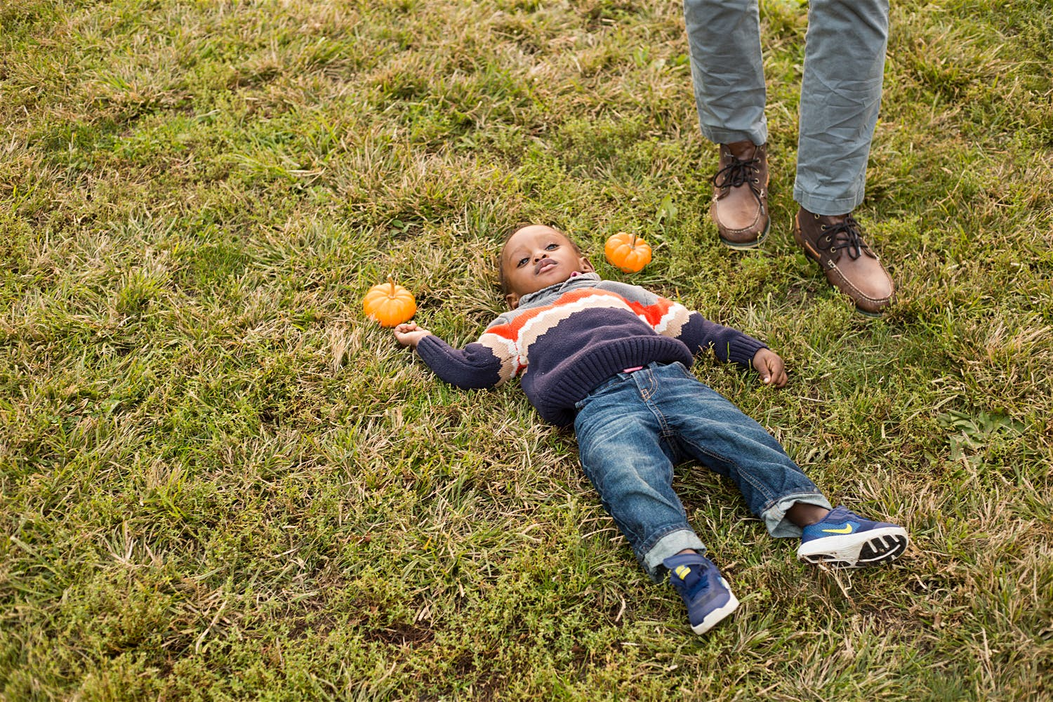 kid lying on the ground with pumpkins new york city brooklyn
