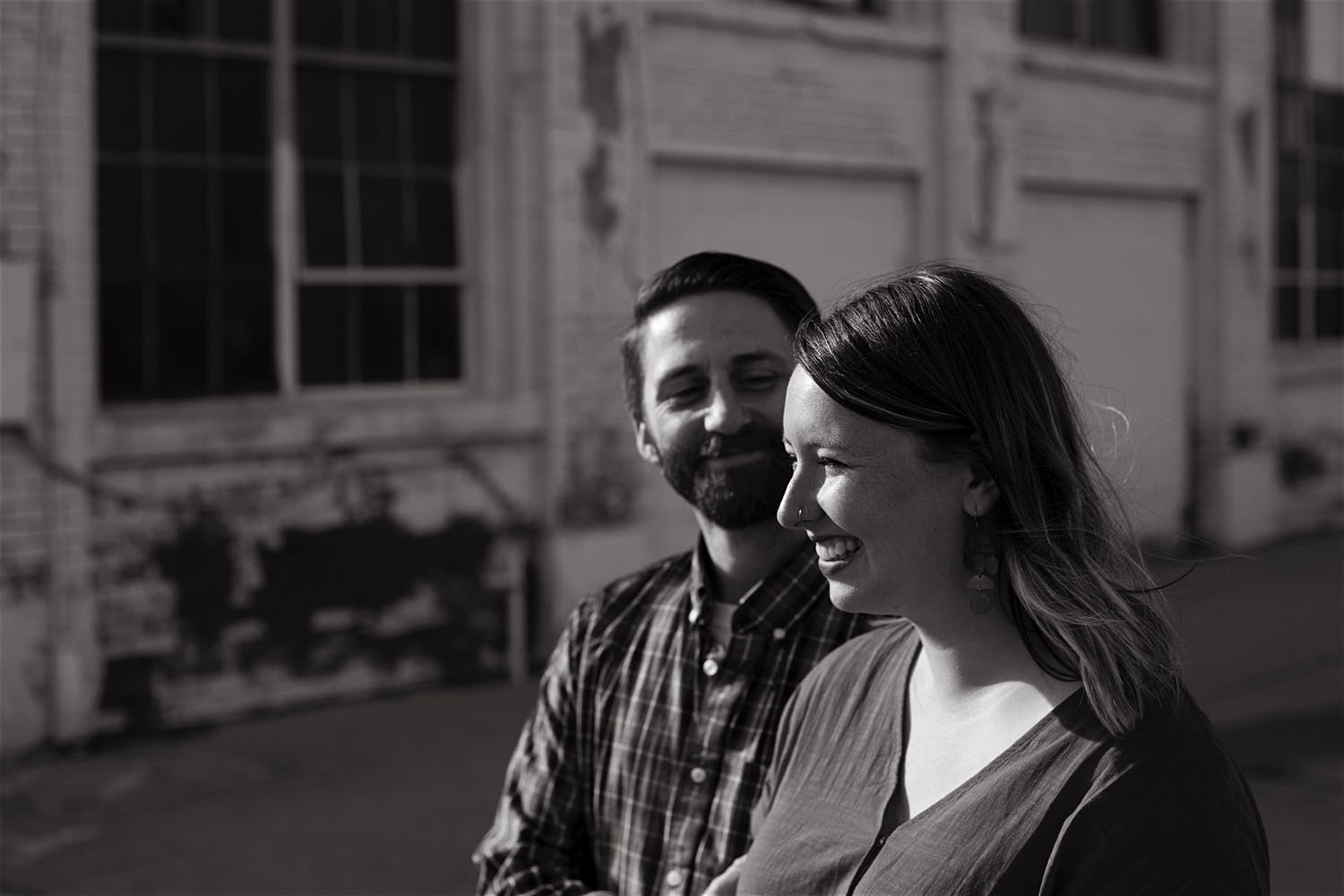 black and white couple portrait in front of abandoned building