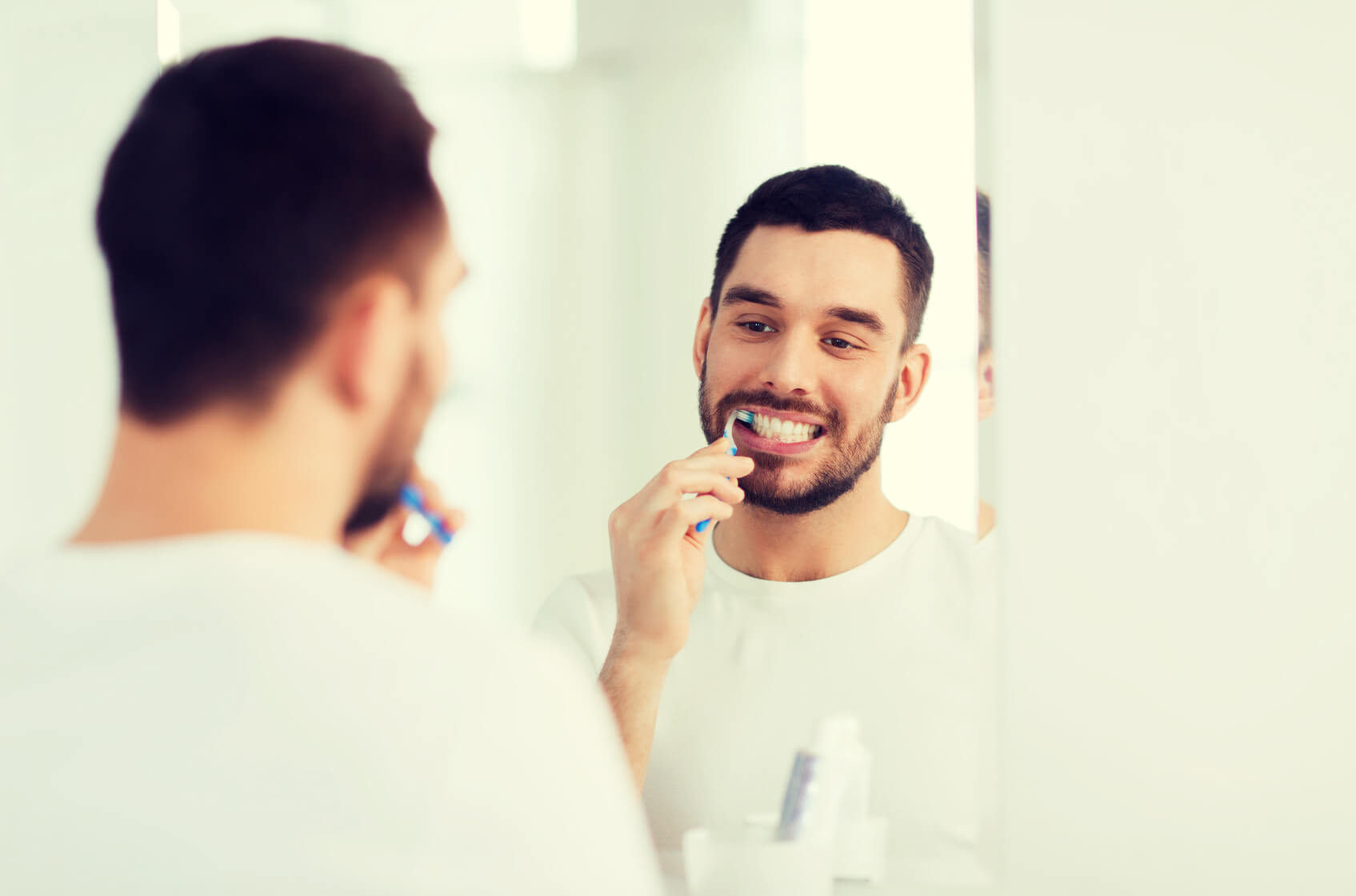 Man maintaining his oral health through brushing teeth