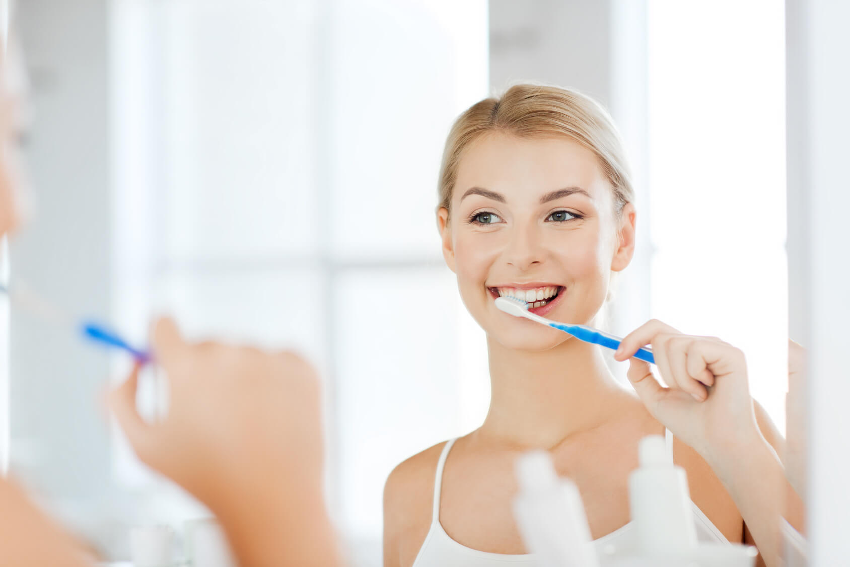 Woman looking in the mirror whilst brushing her teeth