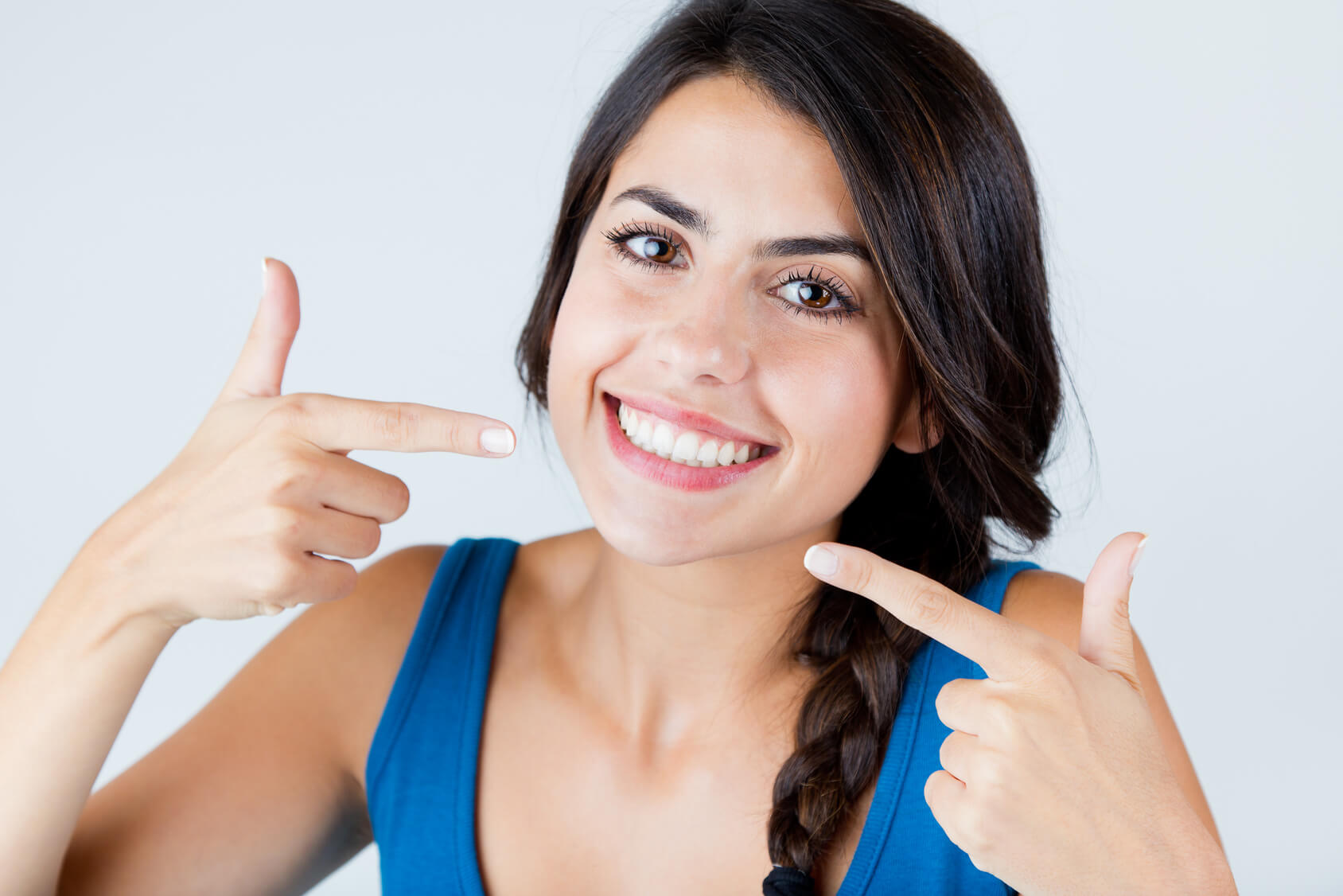Young woman pointing at her teeth after treatment for oral infection