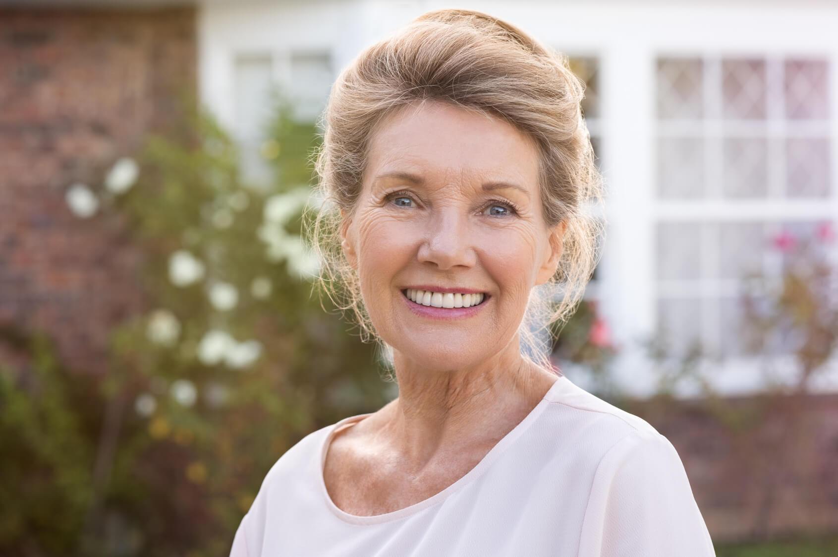 Older lady smiling after having dental implant treatment
