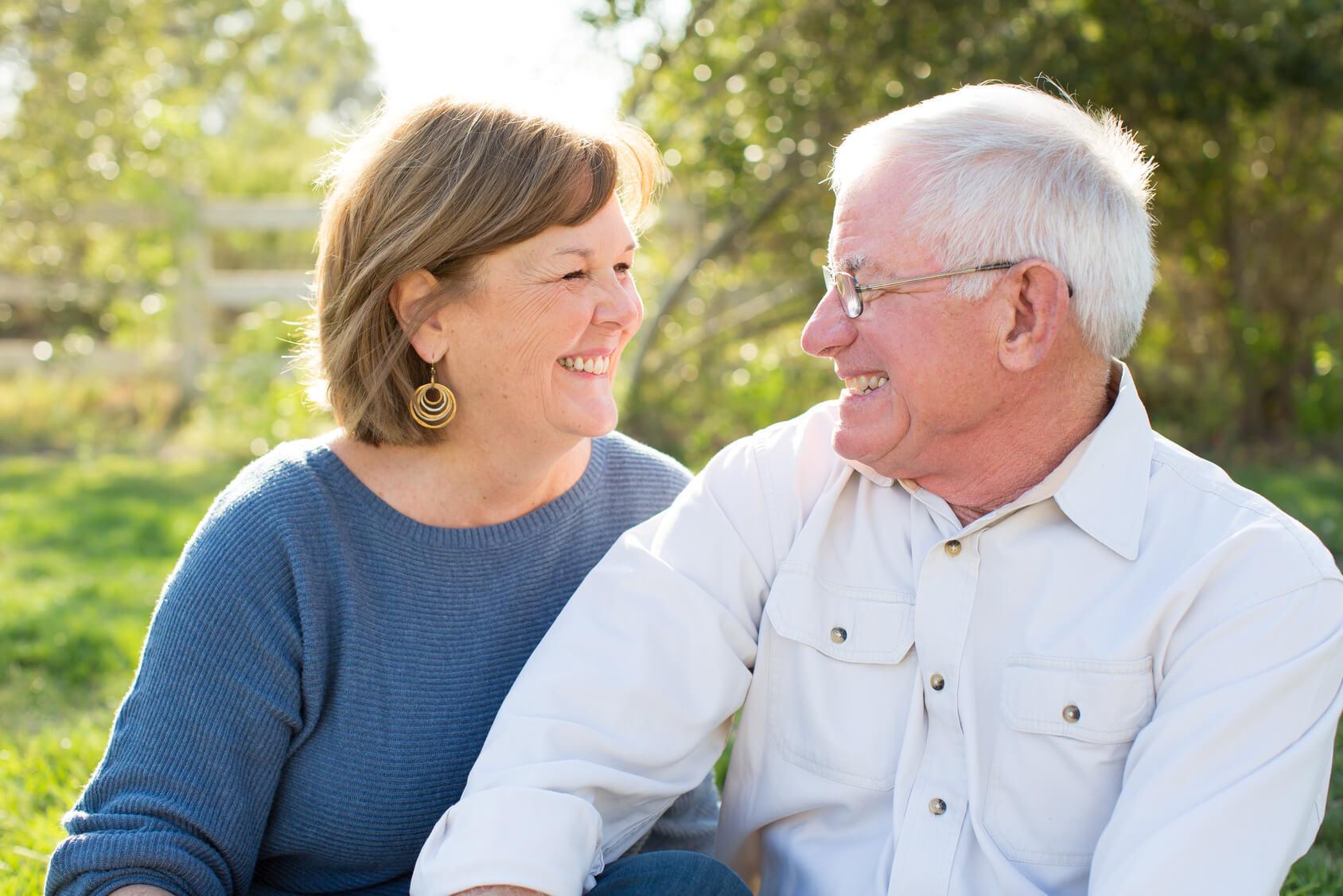 Happy couple in the garden wearing comfortable, custom-made dentures