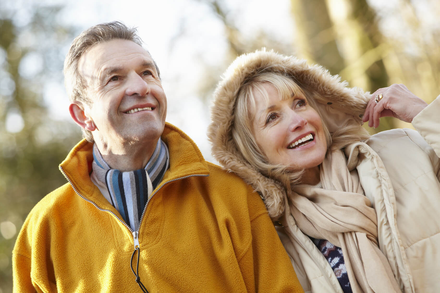 Smiling couple outdoors after replacing their teeth with dentures