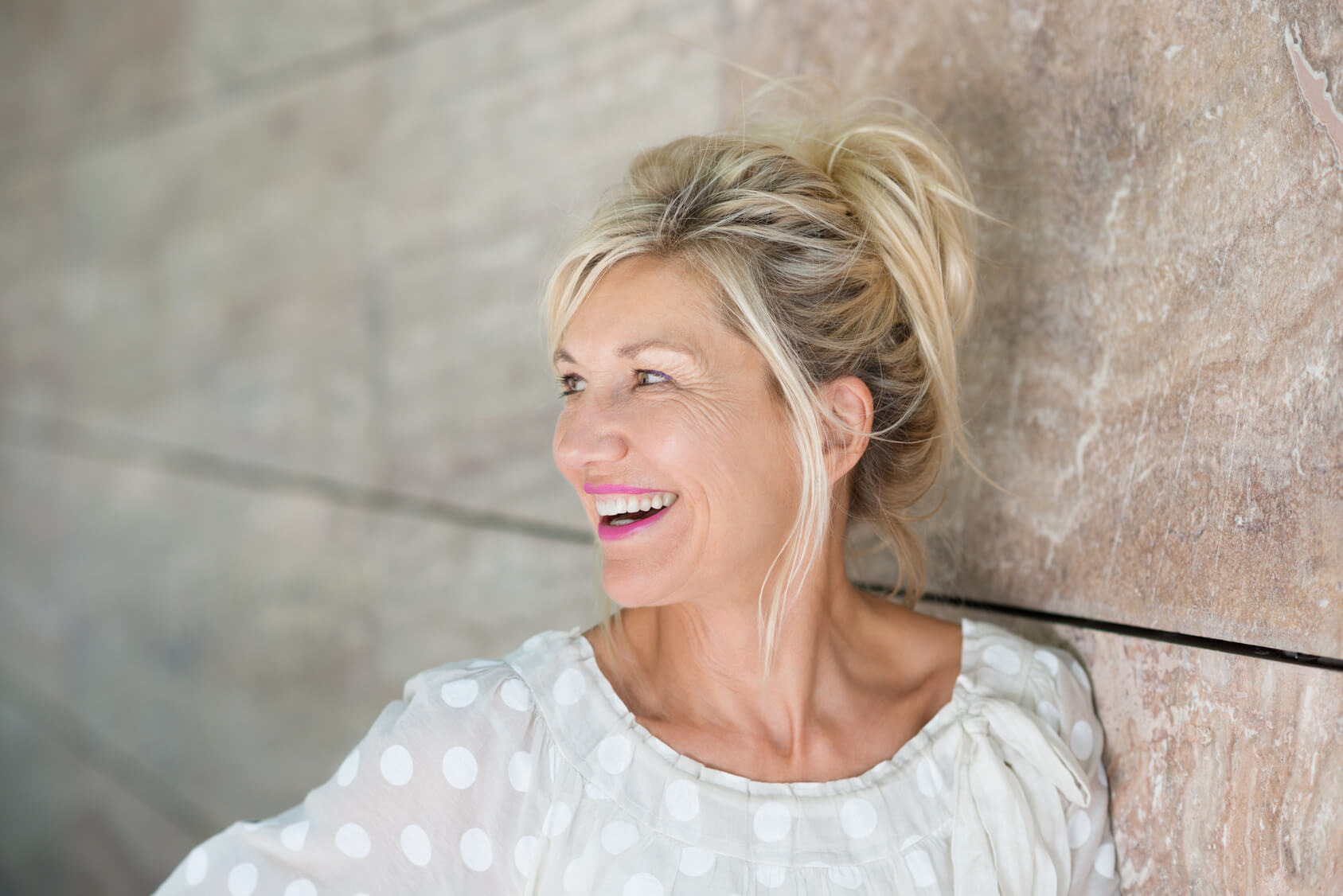 Attractive older lady against a wall and smiling after having dental bridge