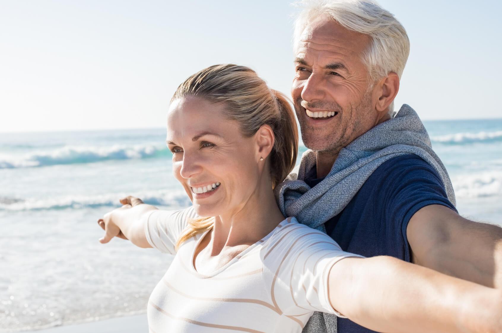 Couple with healthy teeth enjoying the coast on holiday