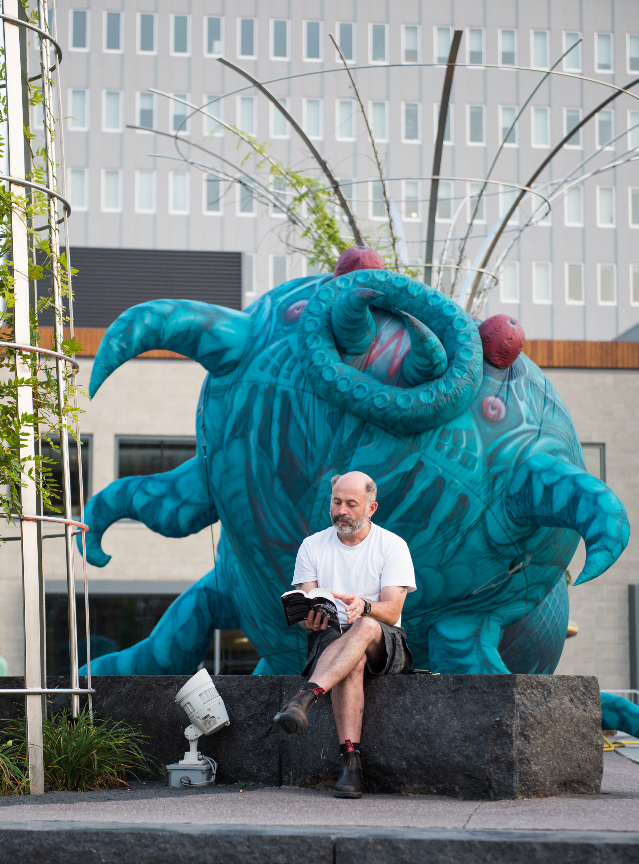 """Gilles """"Lubrick"""" Econard of Plasticiens Volants reads as he waits to perform. Plasticiens Volants has performed across the globe, including the 2016 Olympic Games in Rio de Janerio."""