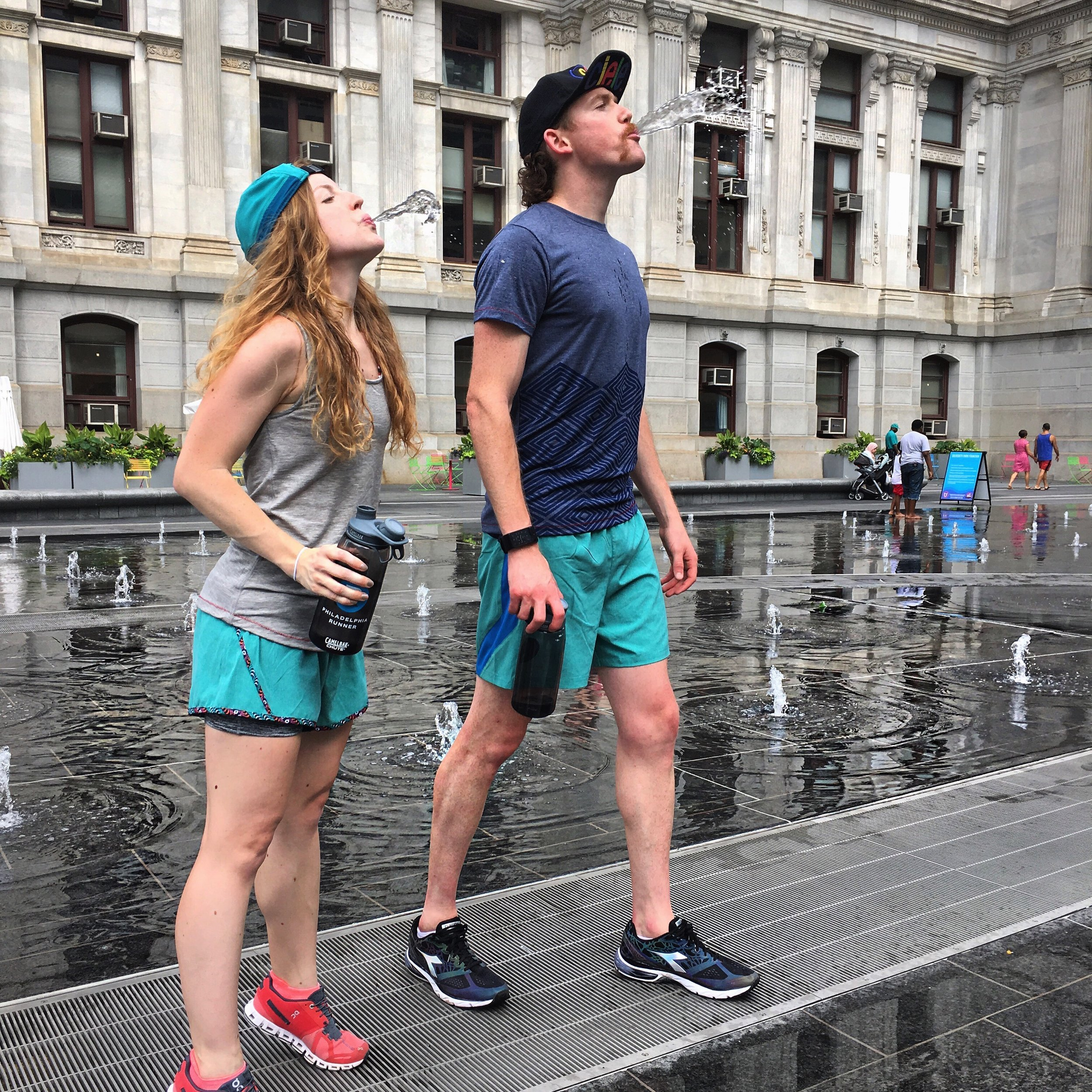 Christine and Breandan are staying hydrated and keeping cool in Ciele Athletic caps and Run Janji apparel. On Running Clouds & Diadora Mythos Blueshield shoes also pictured.