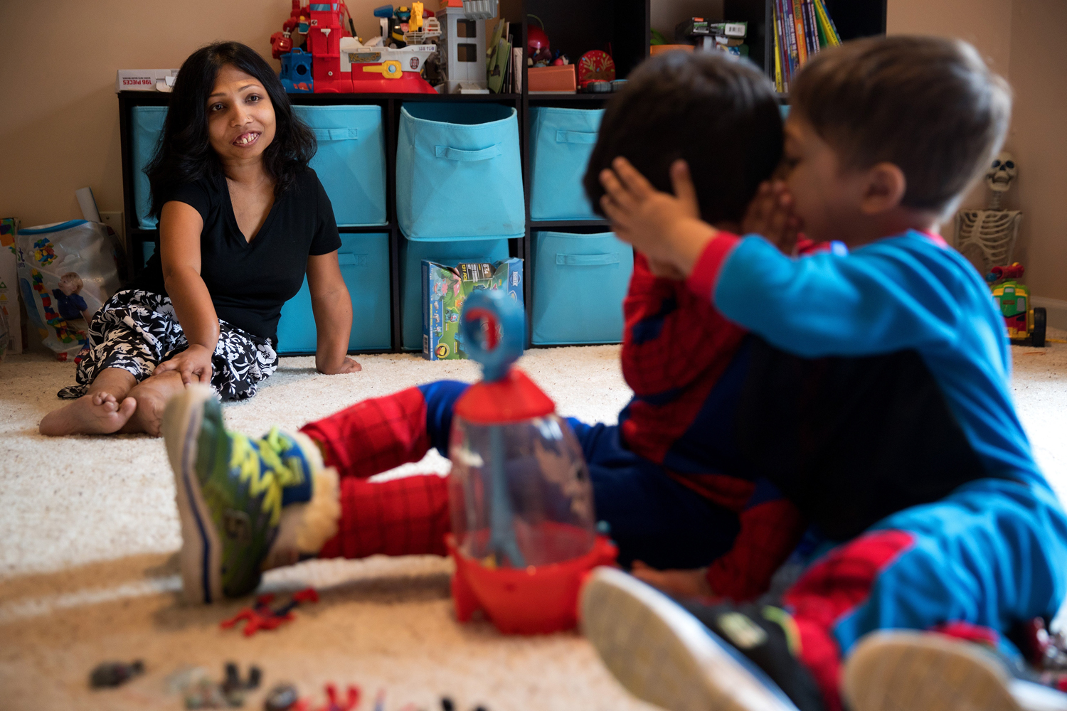 Neena Nizar, whose Jansen's went undiagnosed in her own childhood in the United Arab Emirates, watches her sons whisper to each other while playing a game with superhero figures in March at their Elkhorn home.