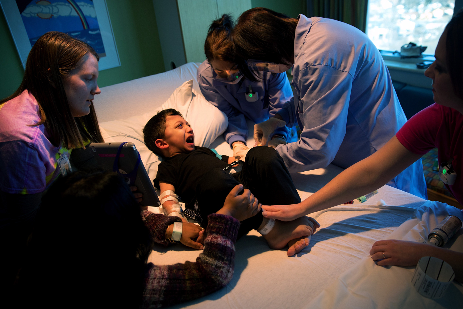 Nurses attempt to connect an IV to Arshaan's left arm before starting an infusion. Small veins that tend to burst frequently and a fear of needles make this process traumatic for the brothers.