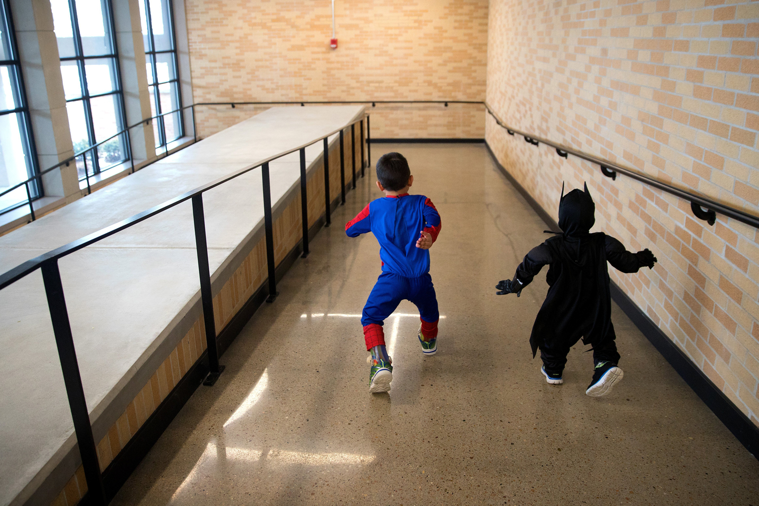 Dressed as superheroes, Arshaan, left, and Jahan play in the hallway at the Omaha Conservatory of Music before their piano lessons in January.