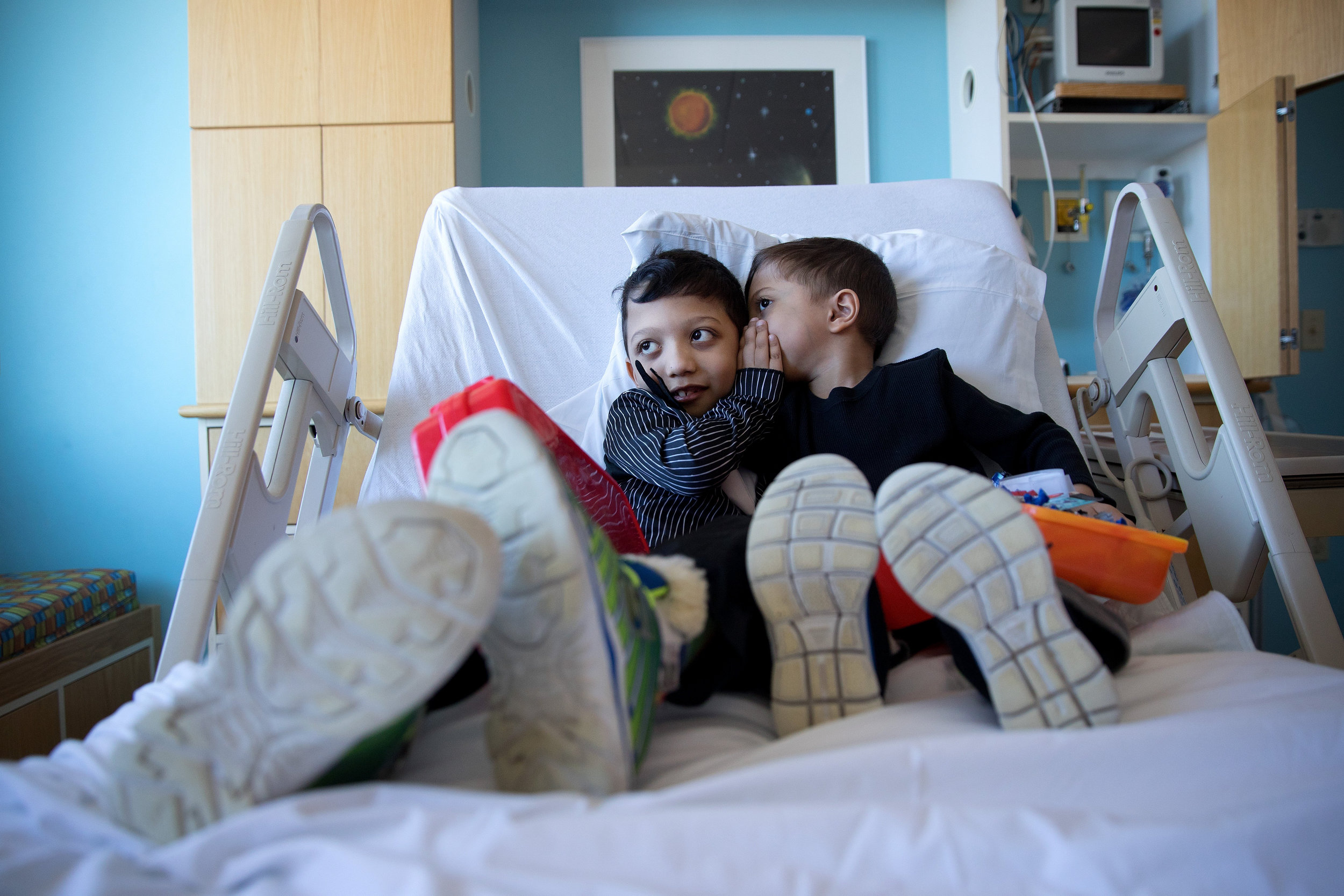 """At Children's Hospital & Medical Center, Arshaan, left, and Jahan tell each other secrets before undergoing infusions to regulate high blood calcium levels. """"Like all rare diseases, there are difficulties that the family has to undergo. There are sacrifices that we make as a family,"""" their mother said."""