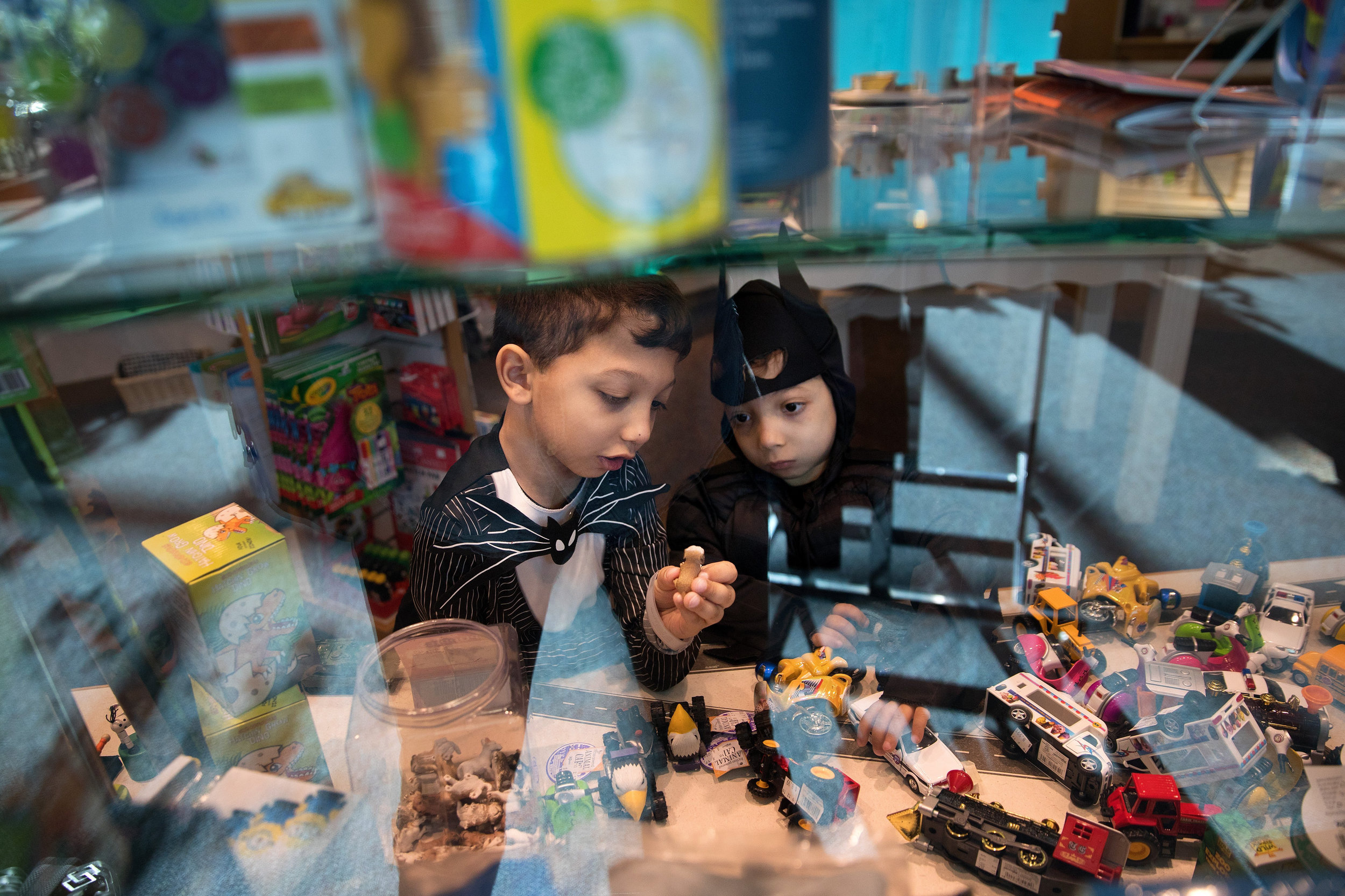 """Arshaan, left, and Jahan explore the gift shop at Children's Hospital & Medical Center. """"So why am I so passionate about driving for a cure? People say you should just accept things the way they are and love your children,"""" Neena Nizar said. """"I do love my children. I love my children tremendously. But I also know what it's like to have pain every day. To not be able to climb up stairs or not be included in certain areas because your feet hurt or your body aches. I do know what it's like."""" She and her sons make up three of the five confirmed cases of Jansen's in the U.S."""