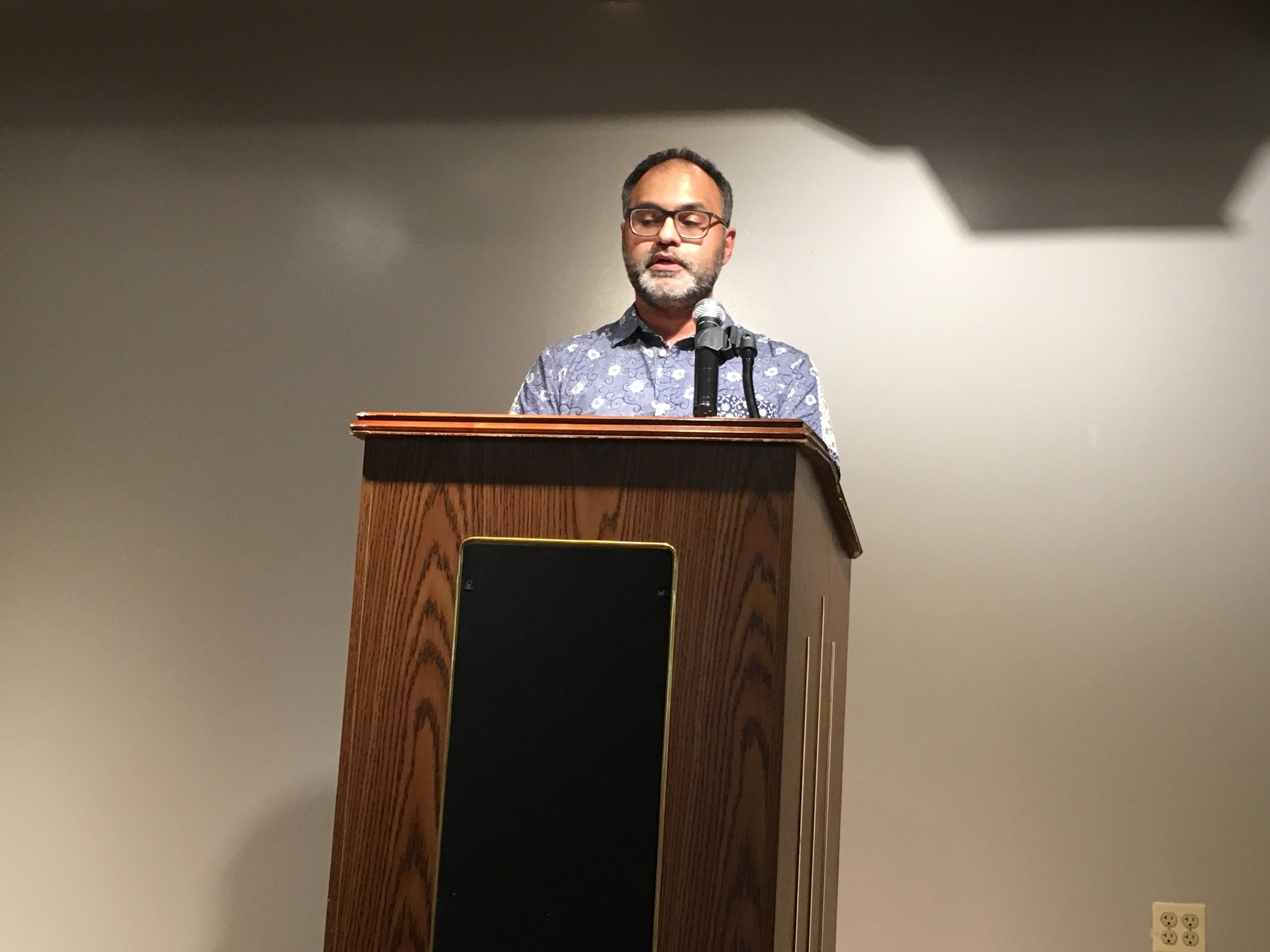 Faisal Mohyuddin introduces the reading he organized, On Migration, Home, and the Search for Belonging at Gibbs-Morrison Cultural Center.