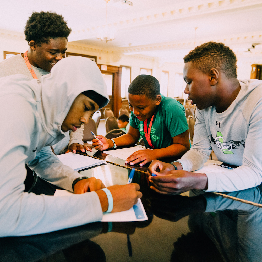 Four young black men working on a project at Next One Up in Baltimore.JPG