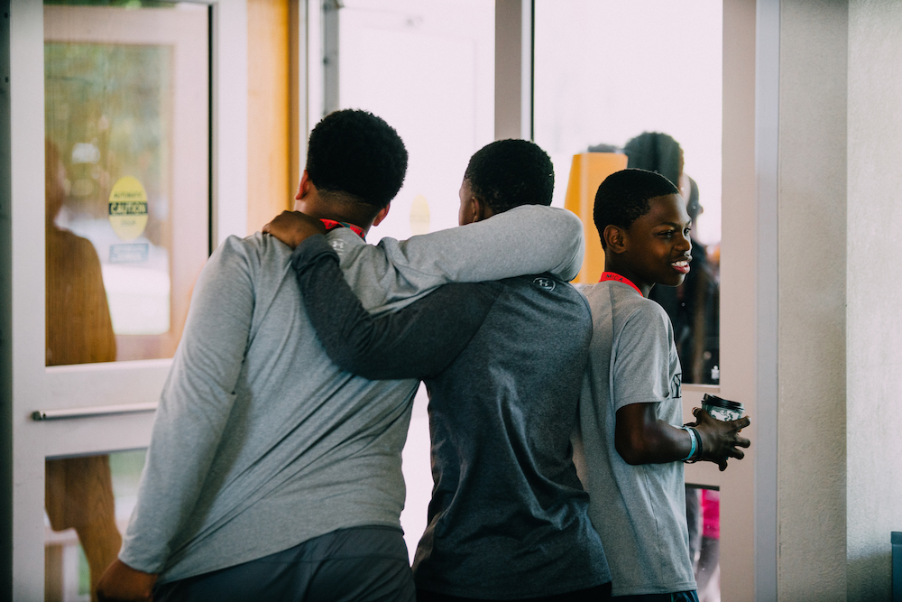 Three young black boys with arms around one another and smiling hanging out.JPG