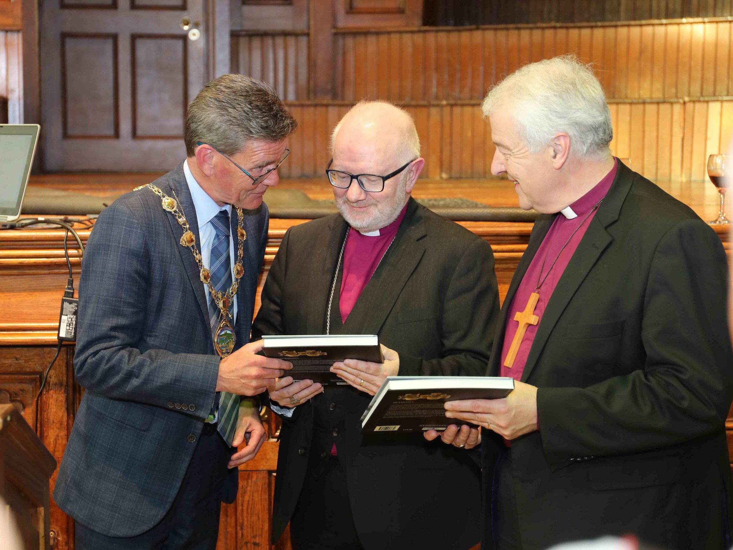 Mayor John Boyle presents a book to Archbishop Richard Clarke and Archbishop Michael Jackson