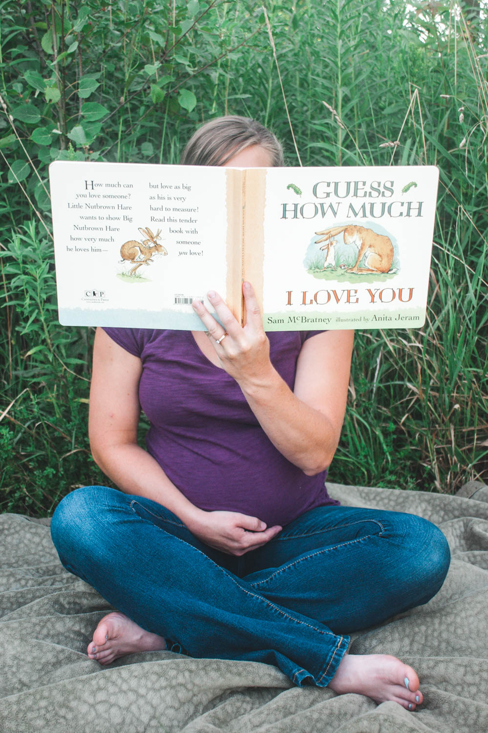 Maternity mom reading unborn baby a book