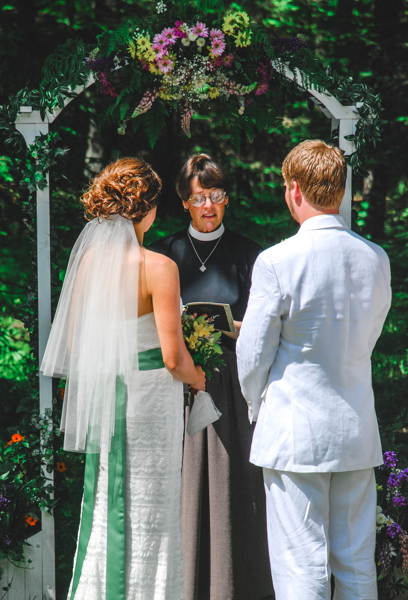 Bride and groom are welcomed by officiant in summer Wisconsin wedding