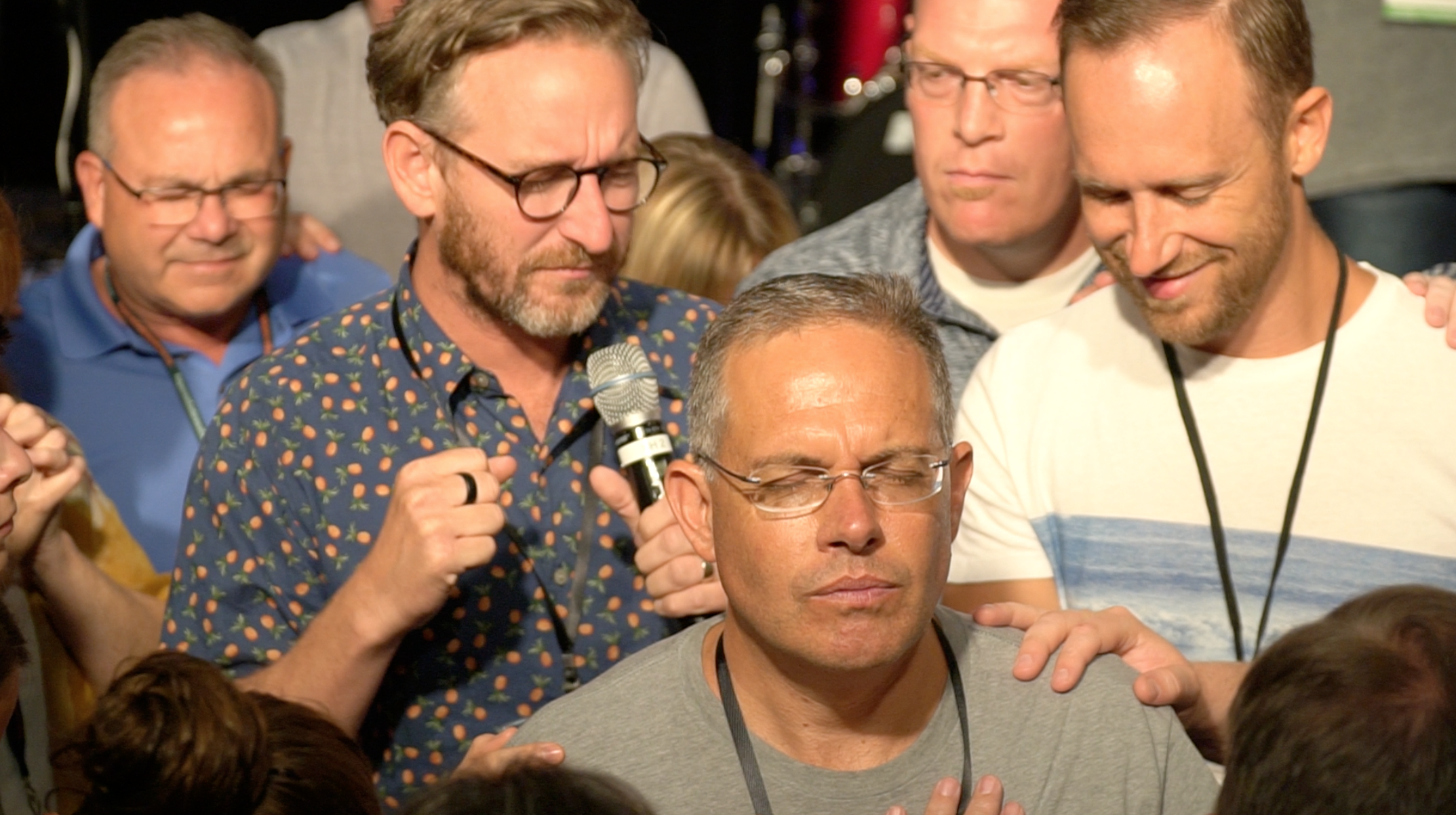 Tom Shaw, Brice Fogle, and several others gather around Scott Marques during the night of prayer at Celebration Southeast.