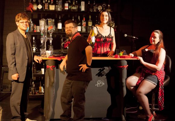[Image description: four actors gathered around a bar set on stage. From left, Michel with light hair wearing a suit and glasses leaning against the bar, Dave with dark hair and goatee in black shirt and jeans with red neckscarf also wearing glasses and leaning against the bar, Karen standing behind the bar with short black hair, wearing a red corset with black accents and holding a bottle of wine, and Madeleine sitting on a bar stool to the right of the bar with arms on the bar with long red hair wearing black corset, denim shorts, red flannel shirt tied around the waist.]